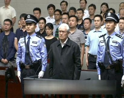 Zhou Yongkang, China's former domestic security chief, stands between his police escorts as he listens to his sentence in a court in Tianjin, China.