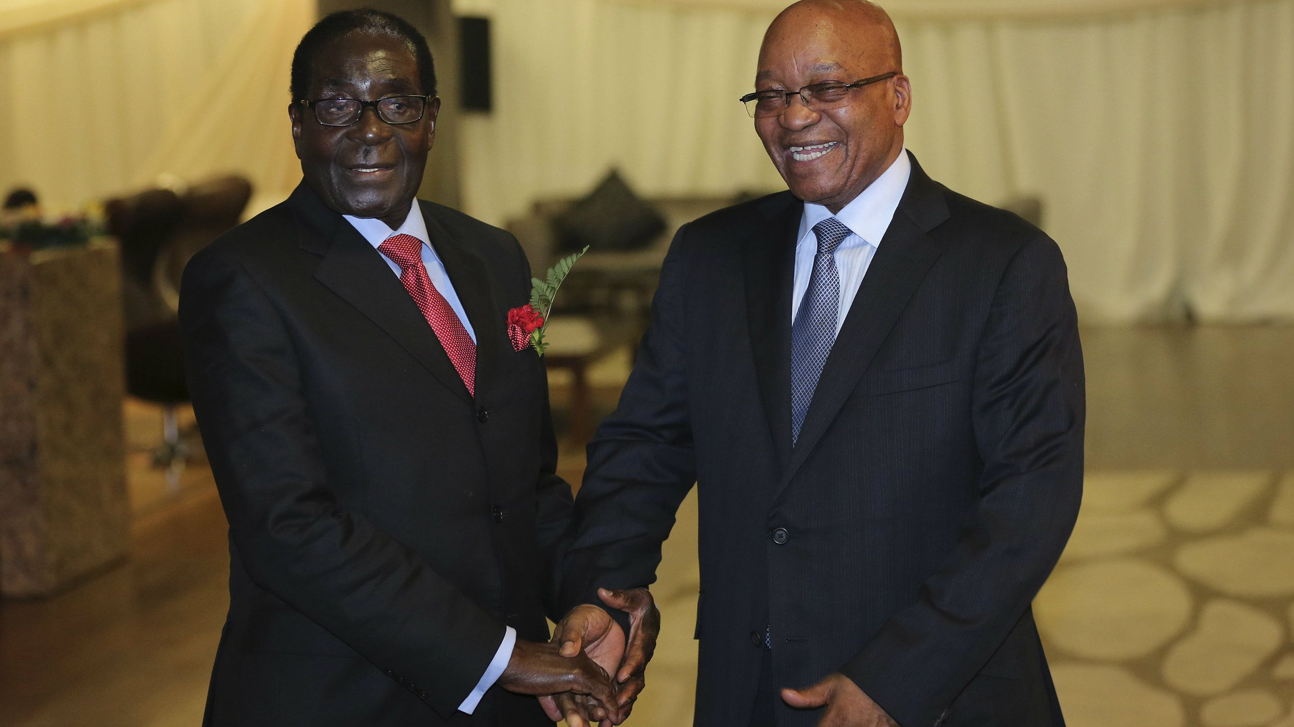 Zimbabwe's President Robert Mugabe (L) is welcomed by his South African counterpart Jacob Zuma