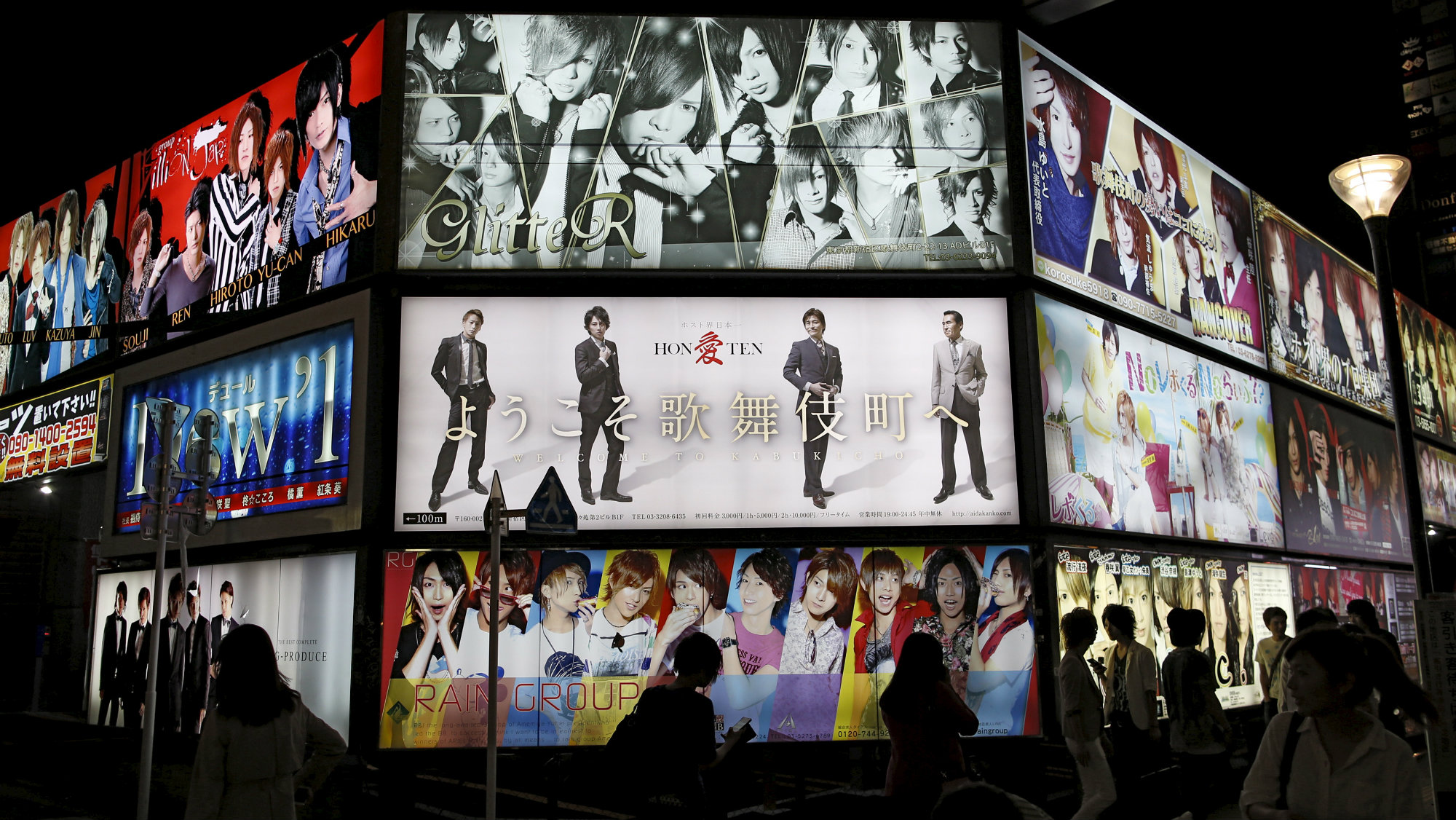 """Passersby are silhouetted in front of an illuminated advertising board of a gigolo club called """"host club"""" in Kabukicho, Tokyo's biggest amusement district, June 12, 2015."""
