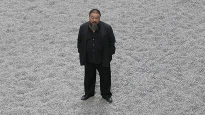 Chinese artist Ai Weiwei poses for a photograph with his new installation entitled 'Sunflower Seeds'.