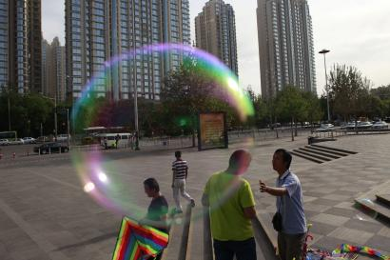 A kite vendor haggles with a customer near a bubble outside a park in Beijing, China, Monday, May 14, 2012. (AP Photo/Ng Han Gua