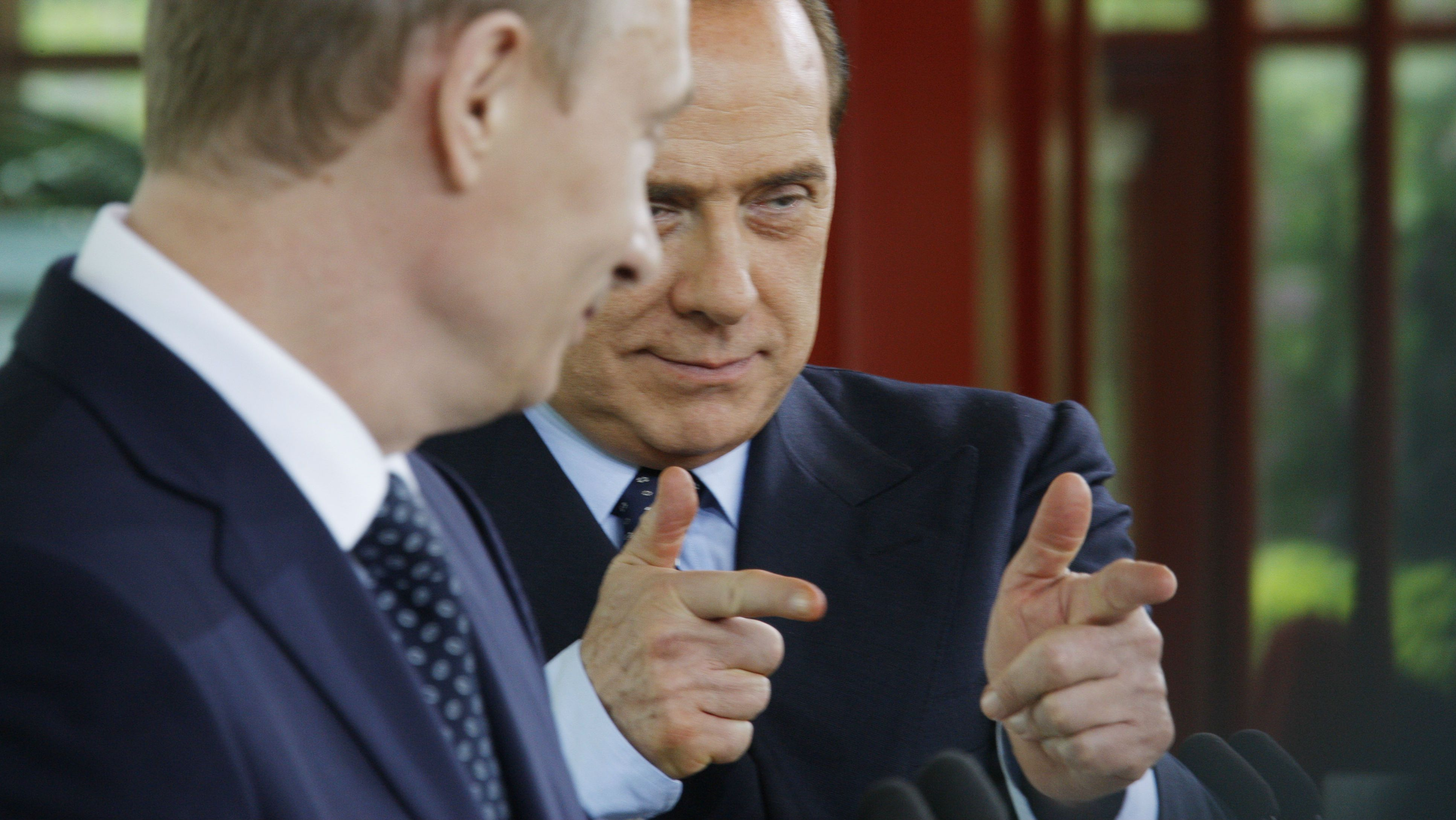 Russia's president Vladmir Putin, left, looks on as Italy's Premier-elect Silvio Berlusconi gestures, during a joint news conference after talks in Berlusconi's Villa Certosa, in Porto Rotondo, on the island region of Sardinia, Italy, Friday, April 18, 2008. (AP Photo/Luca Bruno)