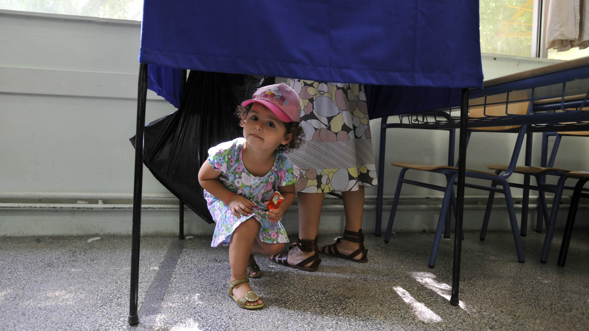 A child looks on from a polling booth as her mother prepares to vote at a polling station during the elections in Thessaloniki, Sunday, June 17, 2012.