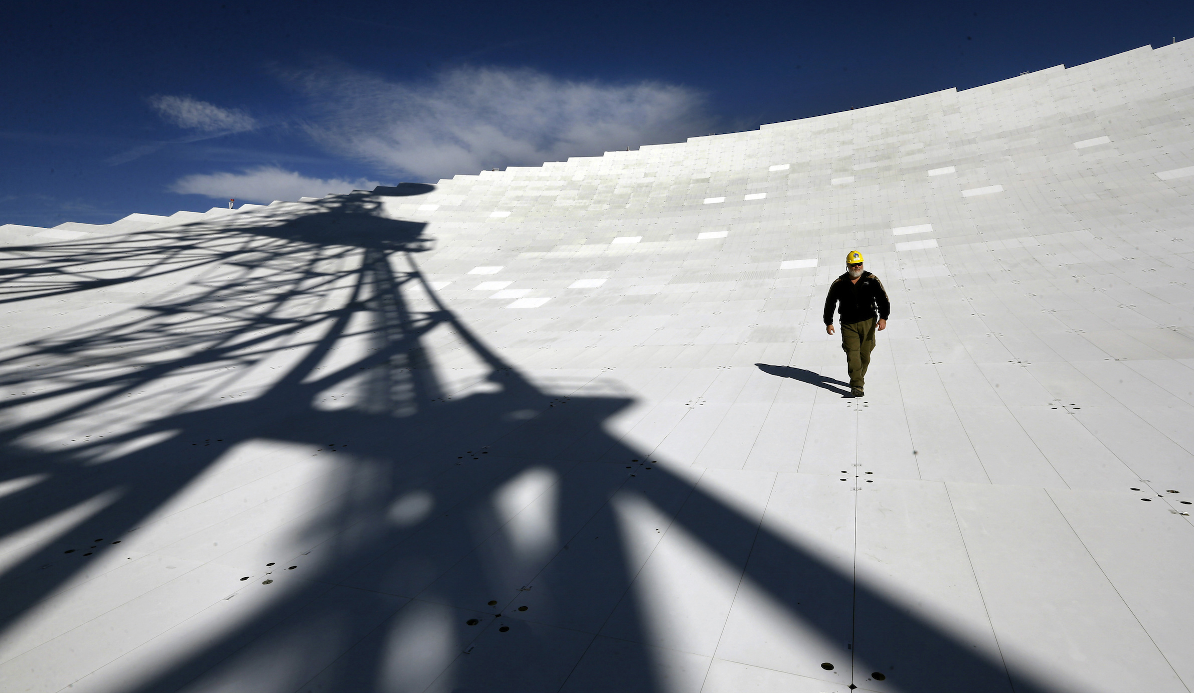 In this Nov. 14, 2013 photo, Michael Holstine, business manager at the National Radio Astronomy Observatory, walks on the 2.3 acre surface of the Robert C. Byrd Green Bank Telescope's dish in Green Bank, W.Va. Scientists use the telescope to conduct a wide range of research, picking up faint signals that aid in the study of the origins and structure of the universe. (AP Photo/Patrick Semansky)