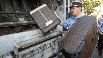 A French customs officer throws counterfeit leather goods into a garbage truck, Monday Sept. 28, 2009 in Cannes, southern France. The items were seized this summer in freight from China at Nice airport, and during regular controls at the French-Italian border. The goods are to be destroyed publicly Monday, as part of a campaign to educate the public about counterfeit goods.