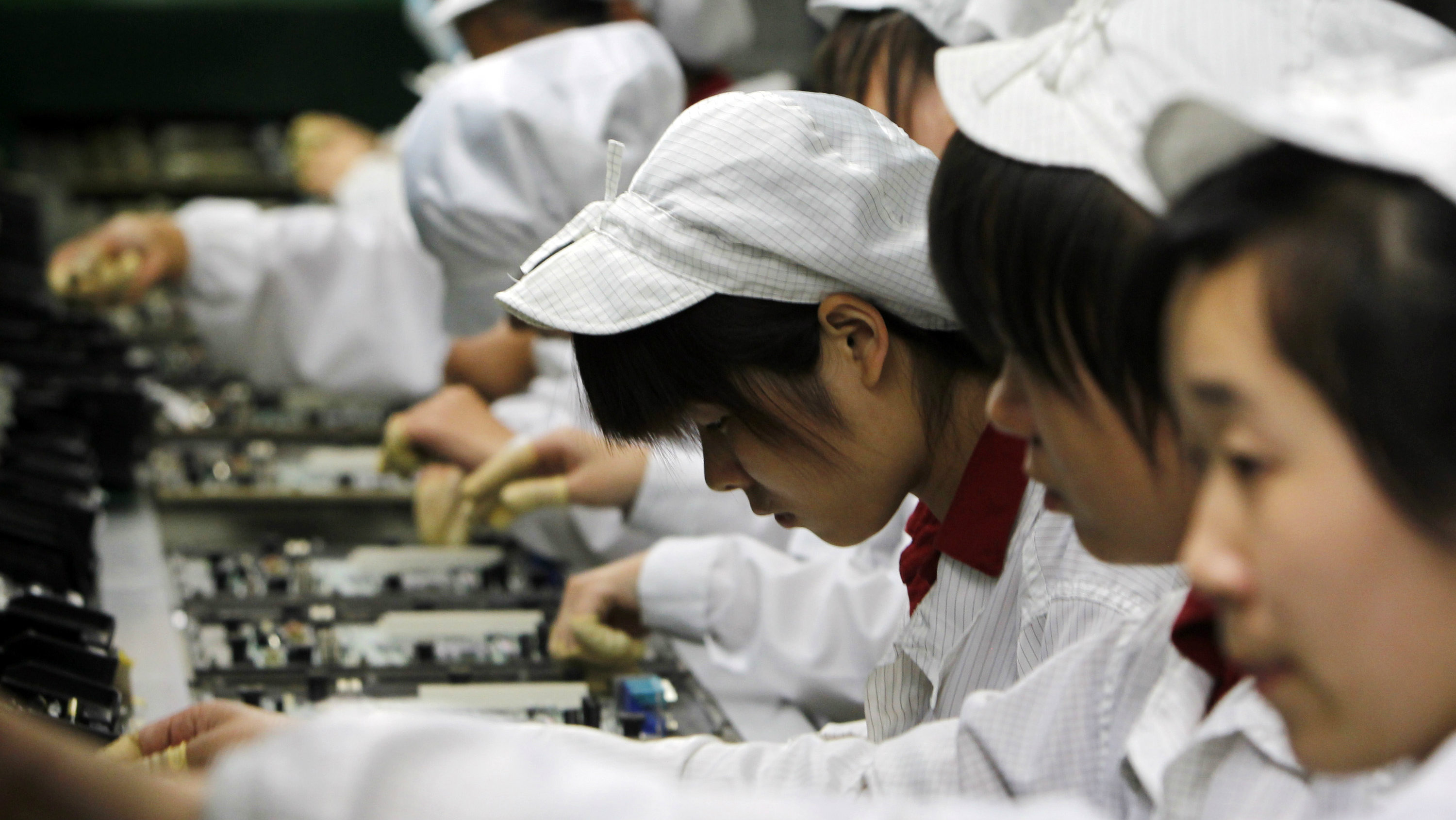Staff members work on the production line at the Foxconn complex, where Apple's iPhones and iPads are created, in the southern Chinese city of Shenzhen.