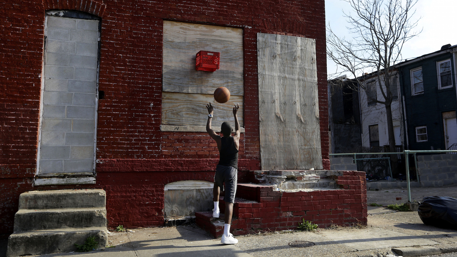 In this April 8, 2013 picture, a boy shoots a basketball into a makeshift basket made from a milk crate and attached to a vacant row house in Baltimore. The U.S. Census Bureau estimates that 20 percent of American children are impoverished. An estimated 16,000 buildings are vacant or abandoned in Baltimore.