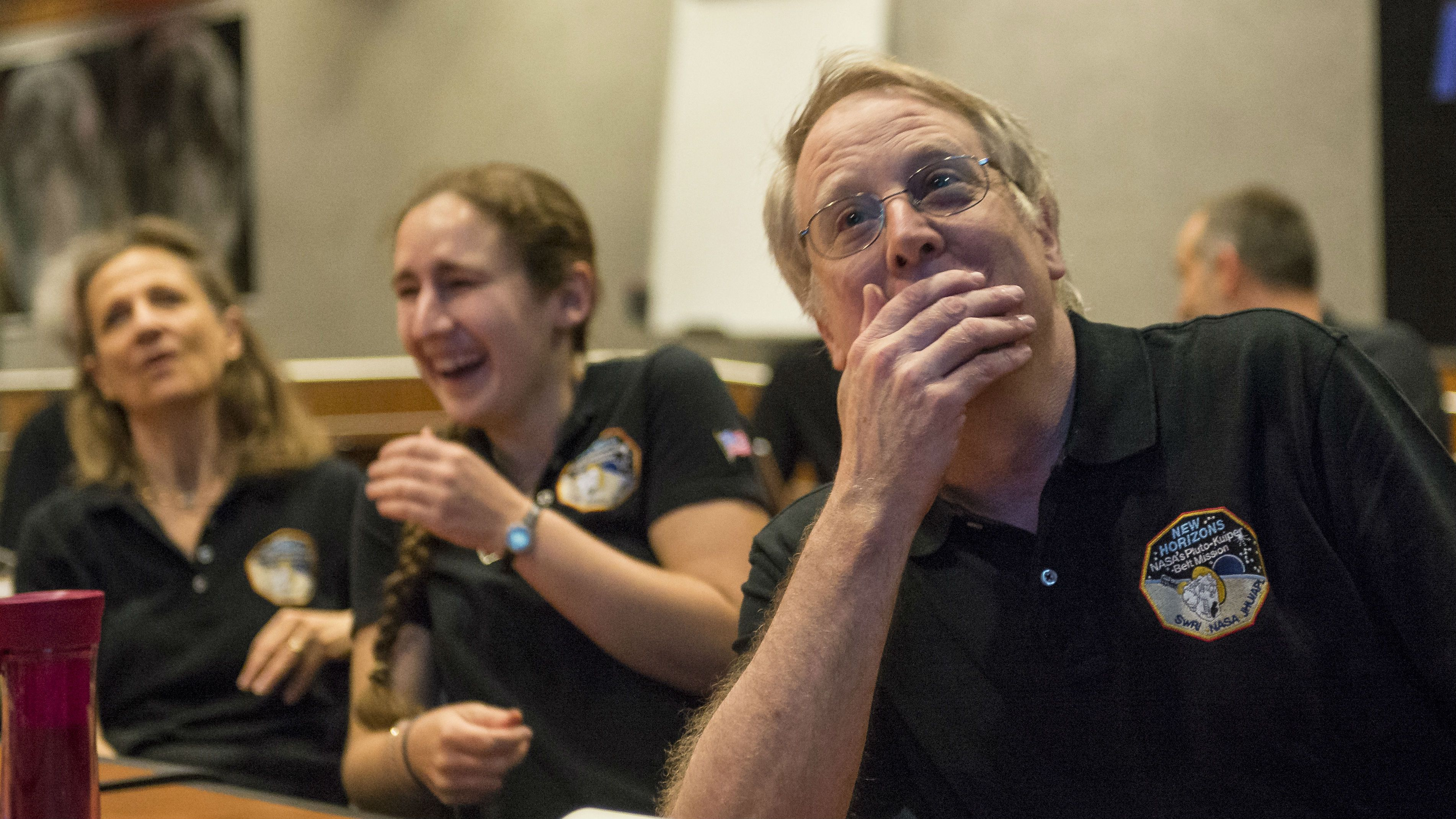 Members of the New Horizons science team react to seeing the spacecraft's last and sharpest image of Pluto before closest approach later in the day, Tuesday, July 14, 2015 at the Johns Hopkins University Applied Physics Laboratory (APL) in Laurel, Maryland. NASA's New Horizons spacecraft was on track to zoom within 7,800 miles (12,500 kilometers) of Pluto on Tuesday. (Bill Ingalls/NASA via AP)