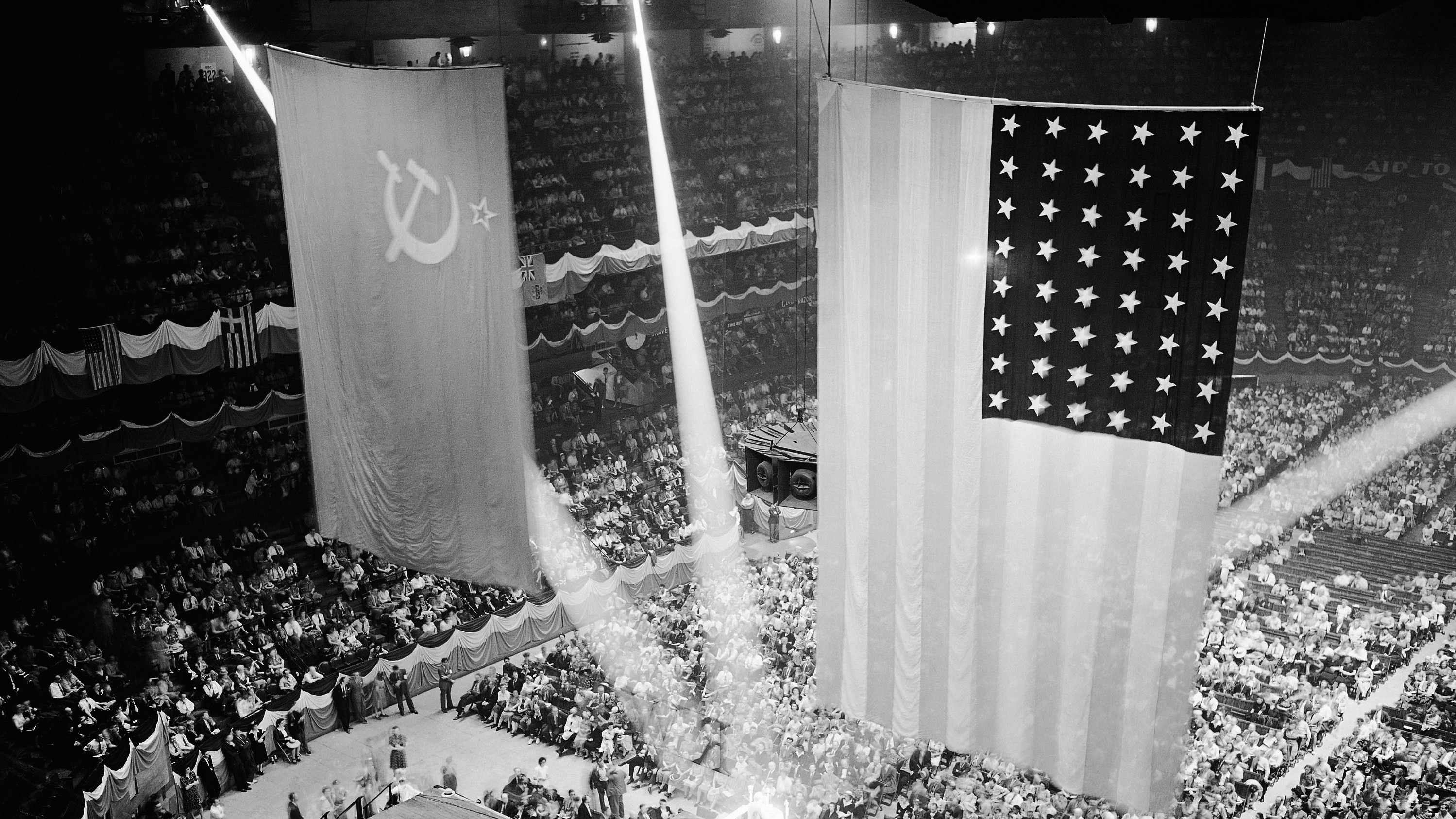 """Long streams of light play on the speaker's platform as the Soviet and American flags hang overhead at the Russian War Relief Rally in Madison Square Garden, New York, June 22, 1942. During the rally a message from President Roosevelt announced that the United States would give Russia aid on the battlefield. Ambassador from Russia, Maxim Litvinov declared that Hitler """"staked his all"""" in his latest offensive."""