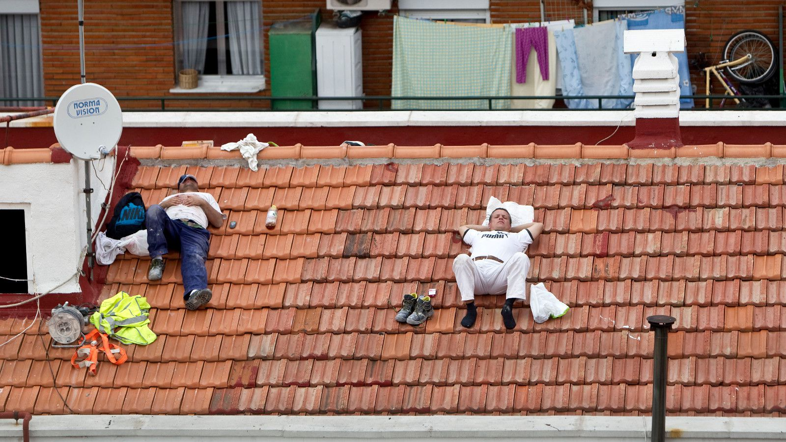 Workers take a nap on a roof in Madrid, Spain. A parliamentary commission is set to approve a report that recommends switching Spain's time zone back to that of Britain, a decision made in World War II to follow Nazi Germany and which experts say has had a dramatic on Spanish eating, sleeping and working habits. (AP Photo/Alberto Di Lolli, File)