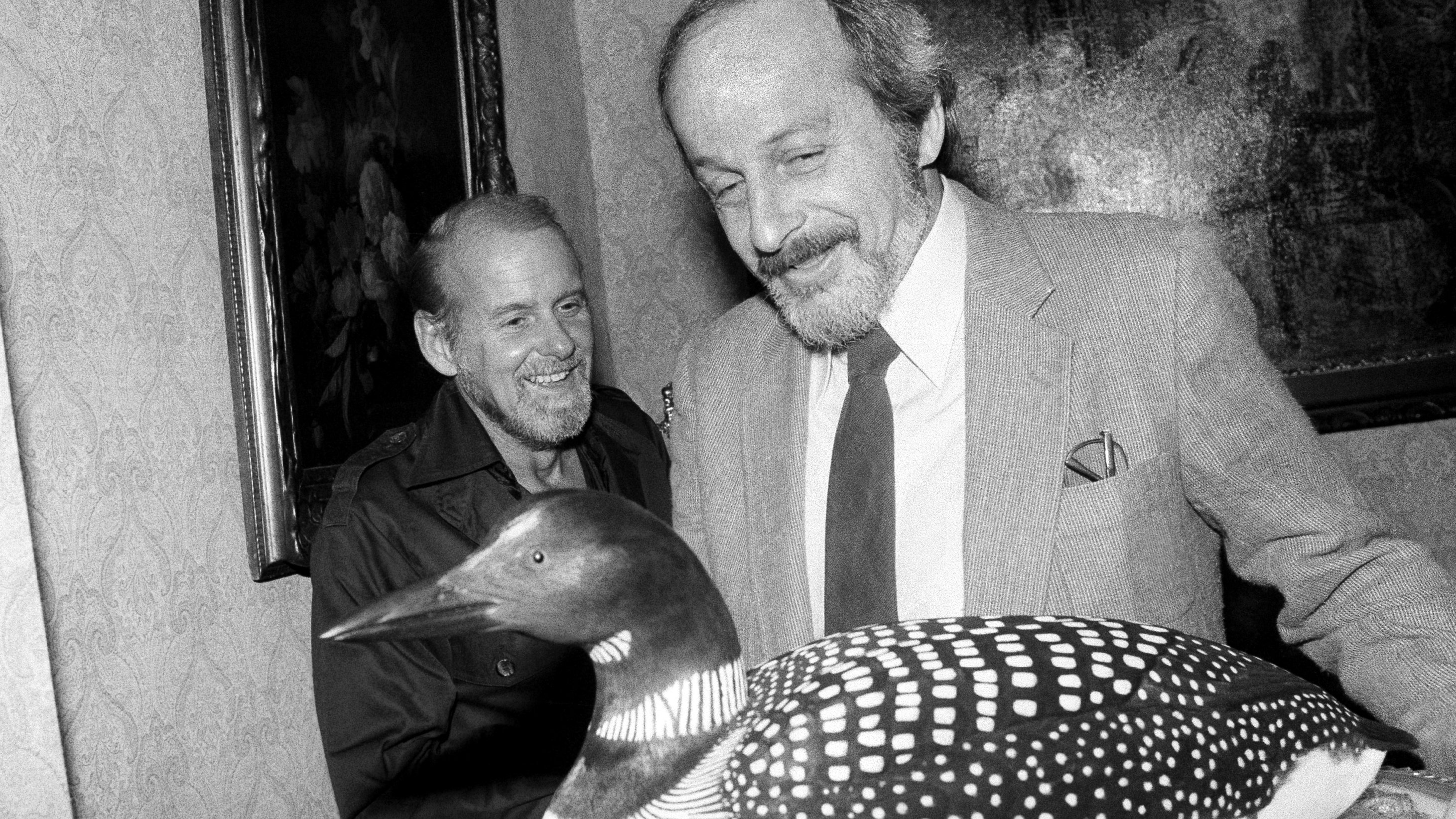 """Author E. L. Doctorow admires a hand-carved loon presented to him at a party in New York on Sept. 25, 1980, while Bob Fosse looks on. Doctorow, author of best seller """"Ragtime,"""" has a new novel which will be on the best seller list next week called """"Loon Lake."""""""