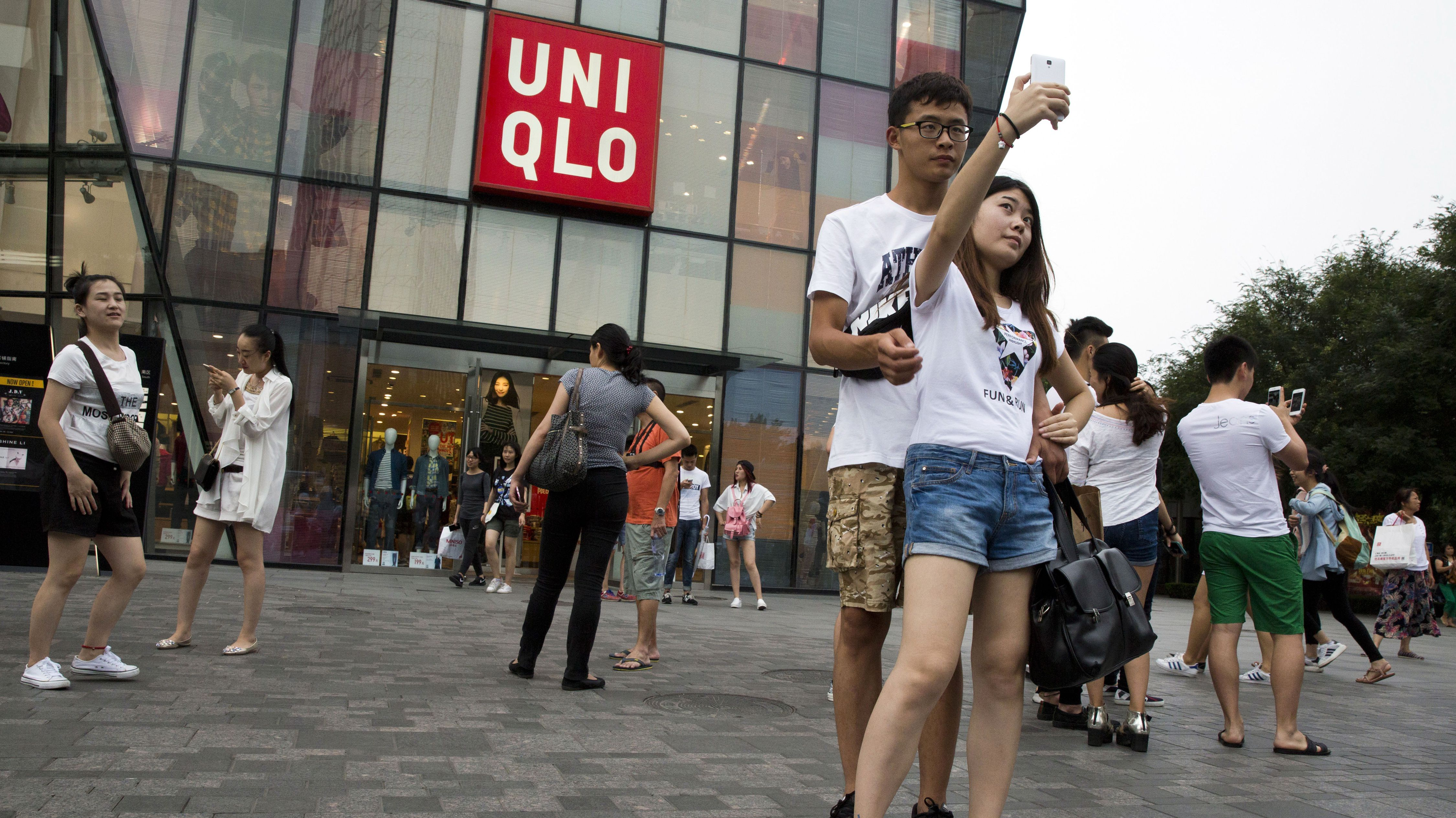 A Chinese couple take a selfie outside the Uniqlo flagship store where a steamy video purportedly taken inside one of its fitting room showing a couple apparently having sex in Beijing, Thursday, July 16, 2015. While online searches for the Japanese clothing brand soared after the viral spread of the video, it has also drawn the concern of the police and China's highest web regulator who are investigating whether it was a vulgar marketing gimmick.