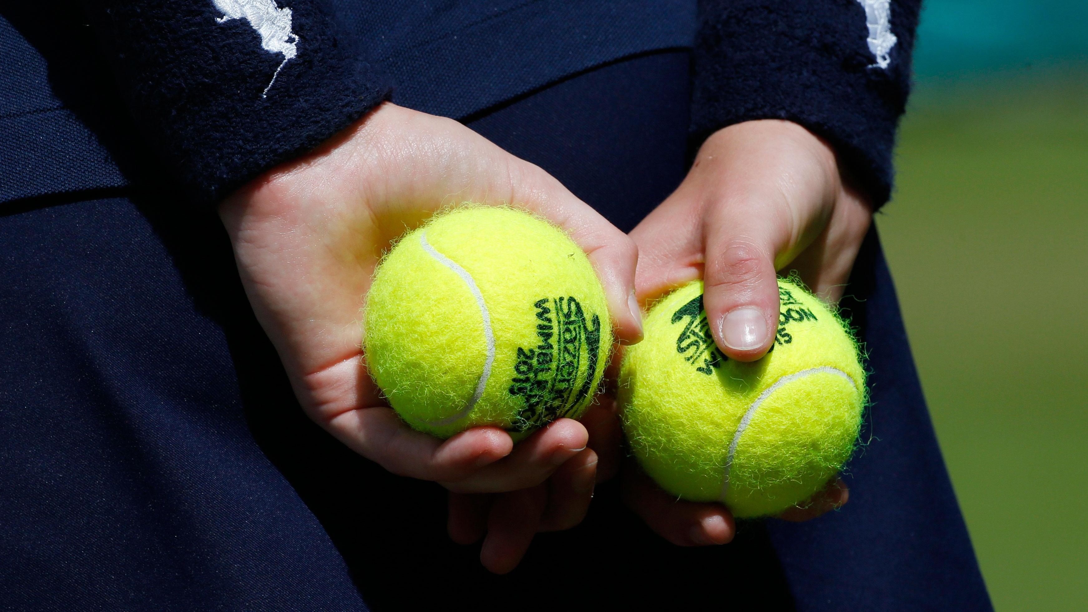 A ball girl holds tennis balls at the Wimbledon Tennis Championships in London