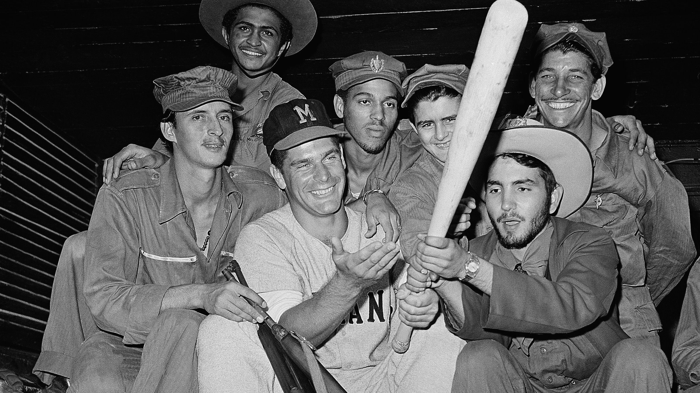 A rebel solider from the Fidel Castro army gets a kick out of trying the bat of Charley Lau, Detroit catcher, playing ball in the Cuban winter league, February 1, 1959. Lau made the boys let him keep their guns so he would be sure and get his favorite stick back.