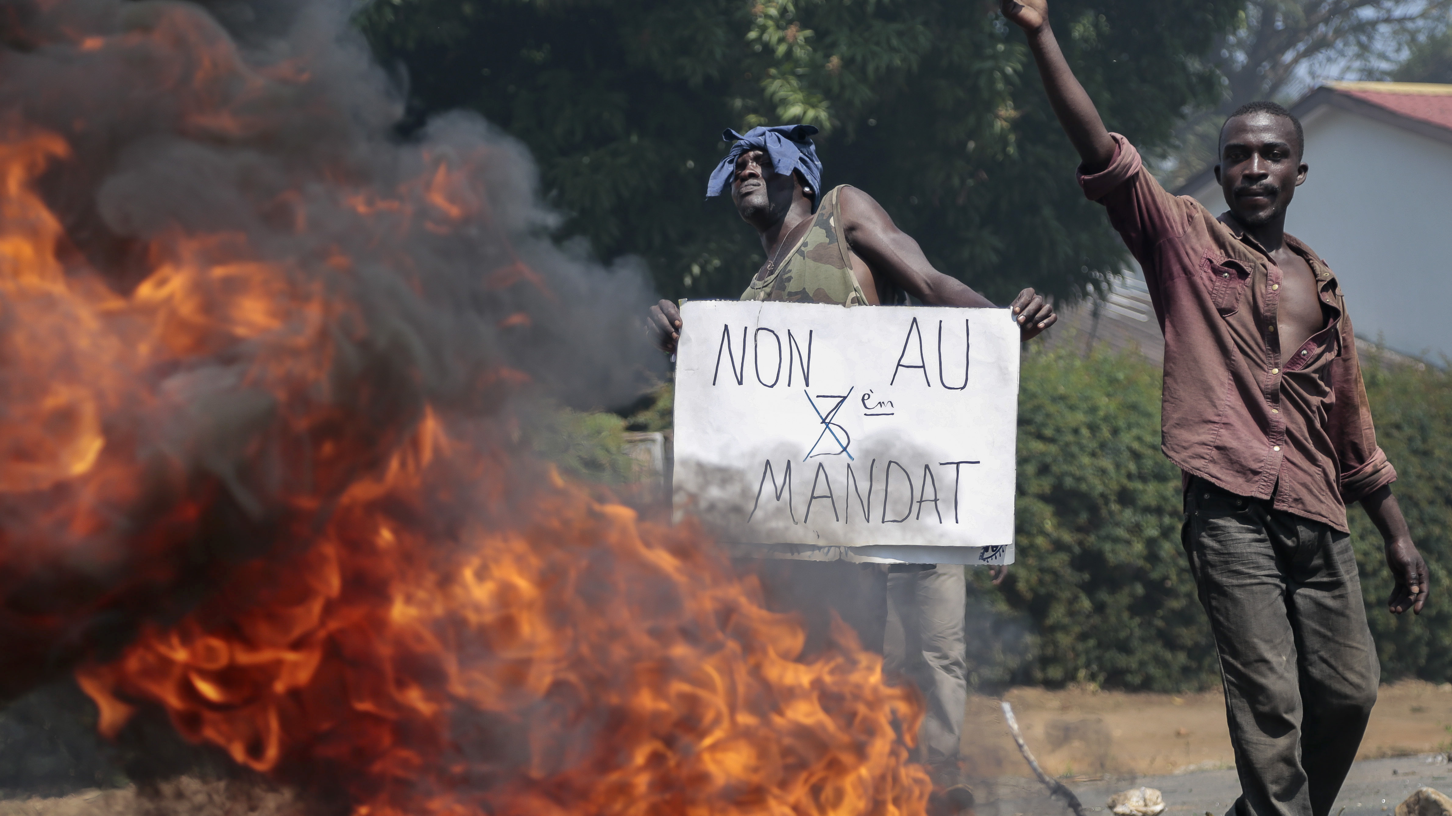 """An opposition demonstrator holds a sign in French reading """"No to a third term"""" next to a burning barricade set by protesters in the Ngagara neighborhood of the capital Bujumbura, in Burundi Wednesday, June 3, 2015."""