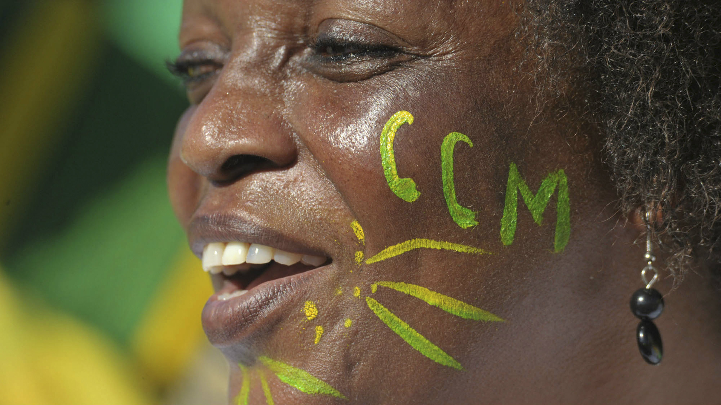 A Supporter of the Tanzania ruling party, Chama Cha Mapinduzi (CCM), cheers as the party's presidential candidate, Jakaya Kikwete, addressed a campaign rally at Jangwani grounds in Dar es Salaam Saturday, Oct. 30, 2010.