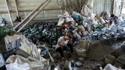 A worker recycles CD players at a workshop in the township of Guiyu in China's southern Guangdong province June 9, 2015.