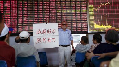 """An investor holds a board showing """"government saves the market so that investors will be happy"""" at a brokerage house in Shanghai, China, July 13, 2015. China stocks, led by small caps, extended their recovery for a third day on Monday, raising hopes that measures taken by Beijing to prevent a full-blown market crash have worked. REUTERS/Aly Song"""
