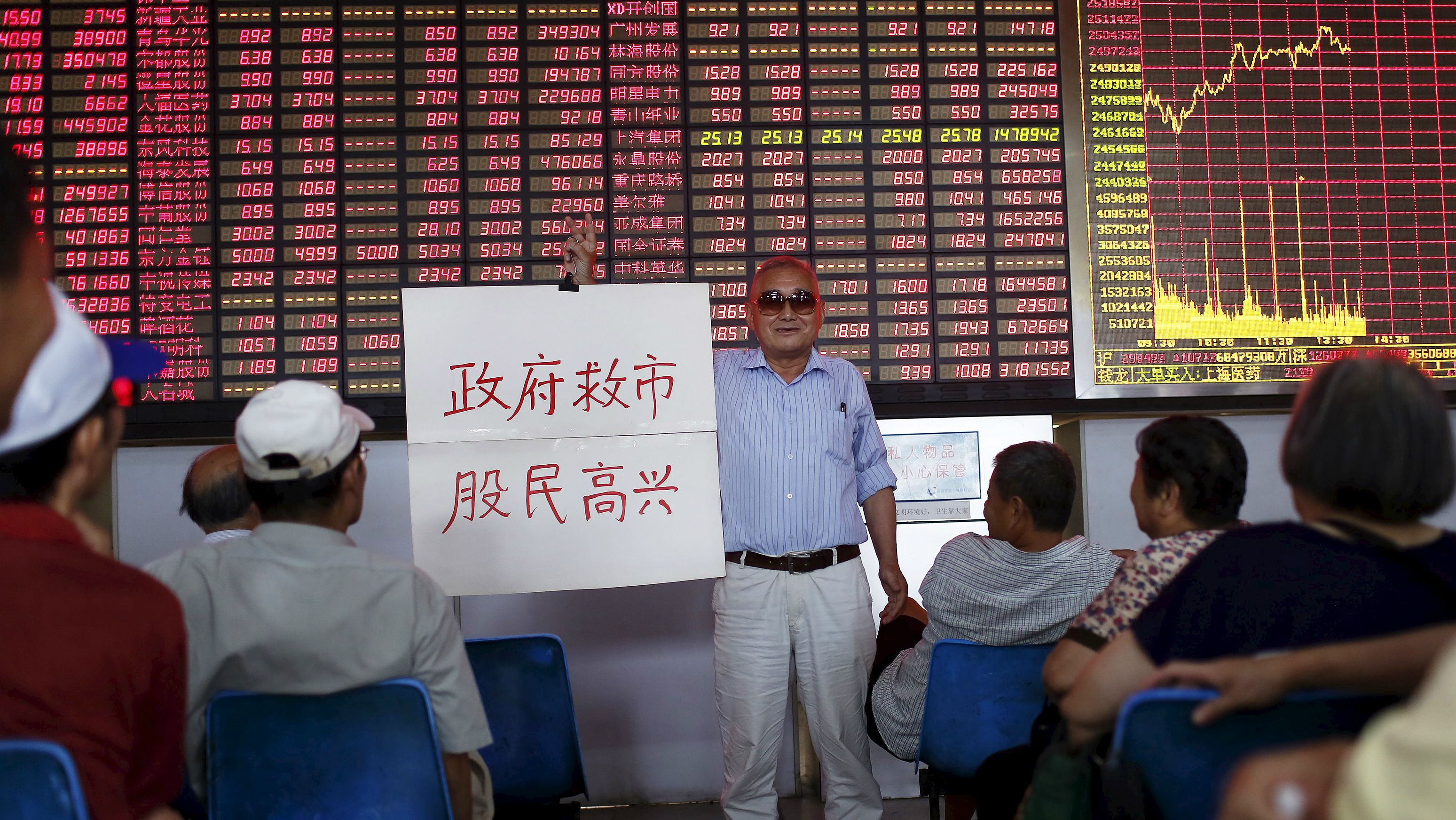 "An investor holds a board showing ""government saves the market so that investors will be happy"" at a brokerage house in Shanghai, China, July 13, 2015. China stocks, led by small caps, extended their recovery for a third day on Monday, raising hopes that measures taken by Beijing to prevent a full-blown market crash have worked. REUTERS/Aly Song"