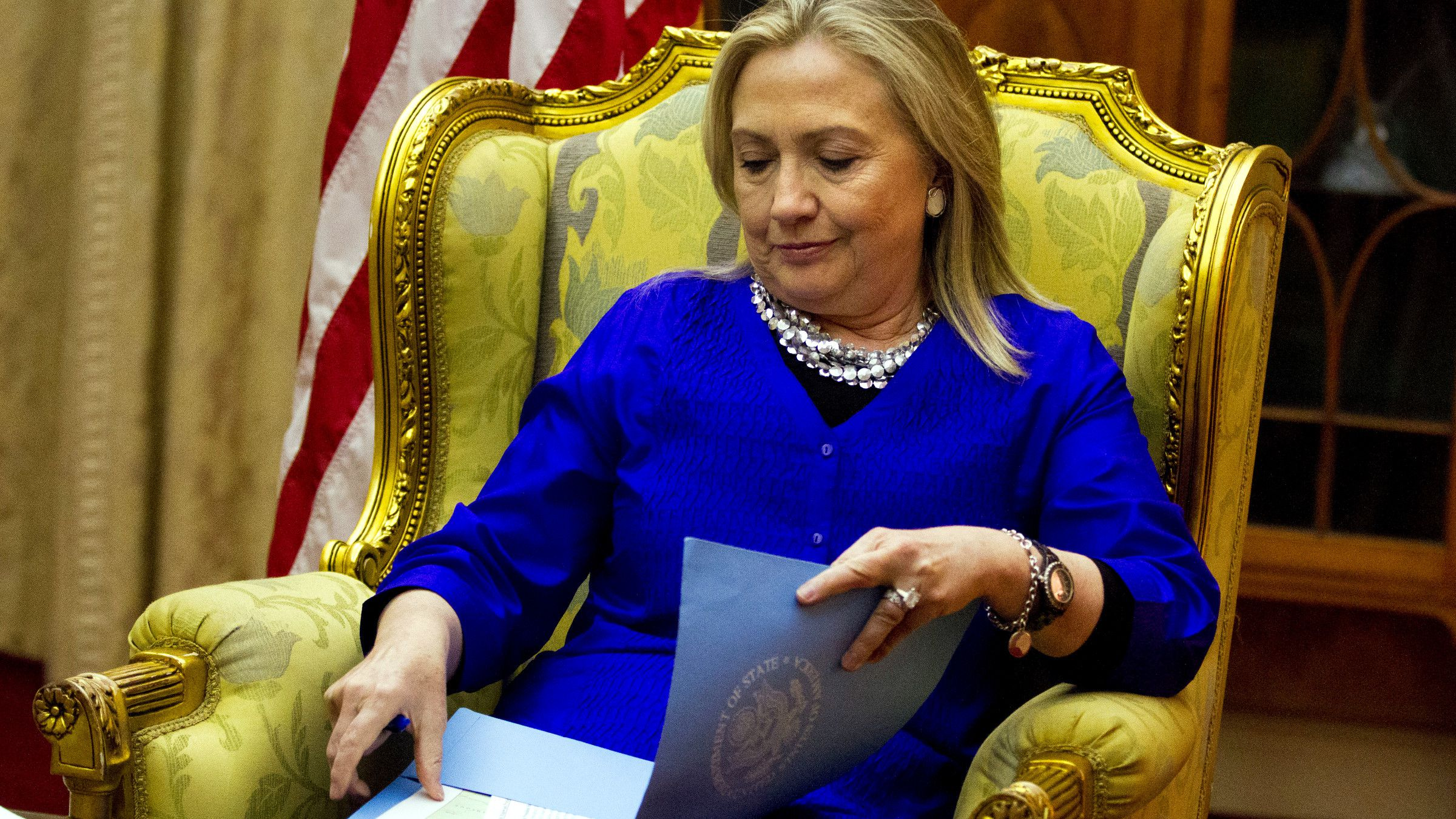 U.S. Secretary of State Hillary Rodham Clinton, opens a folder full of papers at the start of a meeting with Malawi's President Joyce Banda, not pictured, at the State House in Lilongwe, Malawi, on Sunday, Aug. 5, 2012. This is the first visit to Malawi by any U.S. Secretary of State.
