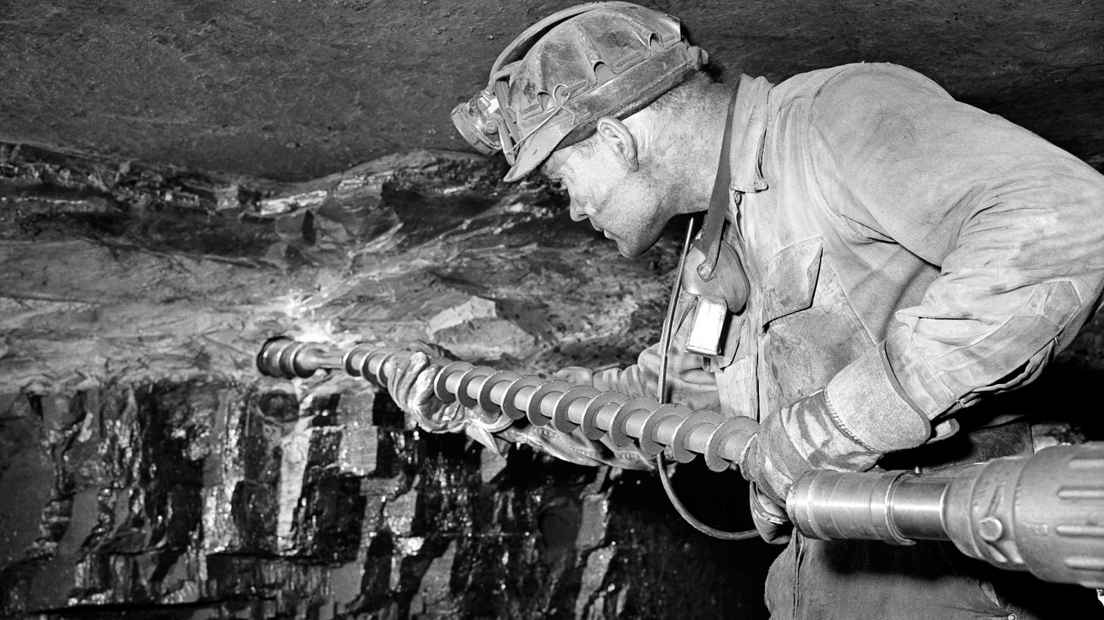 Driller Granville Jackson uses a long auger in a coal mine.
