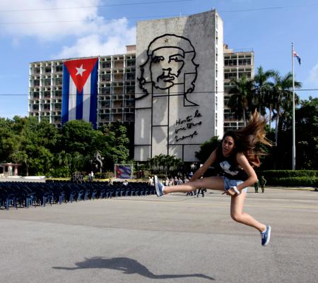 """Carolina, a tourist from Chile, jumps while having her picture taken by a friend before a tribute to revolutionary leader Che Guevara in front of the Cuban Interior Ministry (MININT) in Havana's Revolution Square October 8, 2013. Forty-six years after he was captured by soldiers in a Bolivian jungle and executed the next day, the Argentine-born Ernesto Guevara De La Serna, AKA, 'Che', is still a national hero in Cuba where he joined Fidel Castro in an armed uprising that ousted a U.S. backed dictator in 1959. Tuesday will be Guevara's 46th death anniversary. The words on the building read: """"Onward to victory, always""""."""