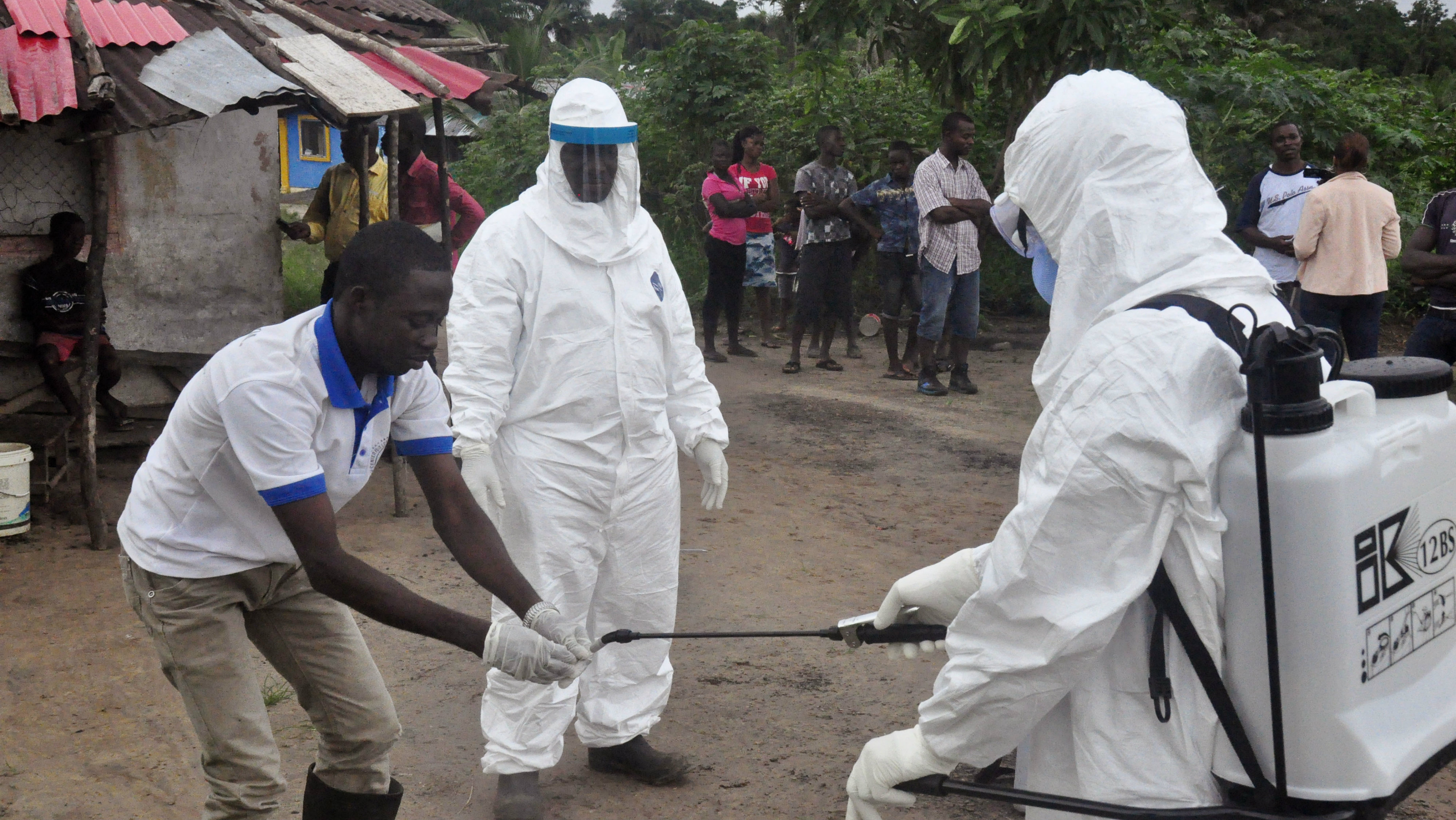 Health workers wash their hands after taking a blood specimen from a child to test for the Ebola virus in an area where a 17-year old boy died from the virus on the outskirts of Monrovia, Liberia, Tuesday, June 30, 2015. Liberian authorities on Tuesday quarantined the area where the corpse of the boy was found, sparking fears this West African country could face another outbreak of the disease nearly two months after being declared Ebola-free. (AP Photo/ Abbas Dulleh)