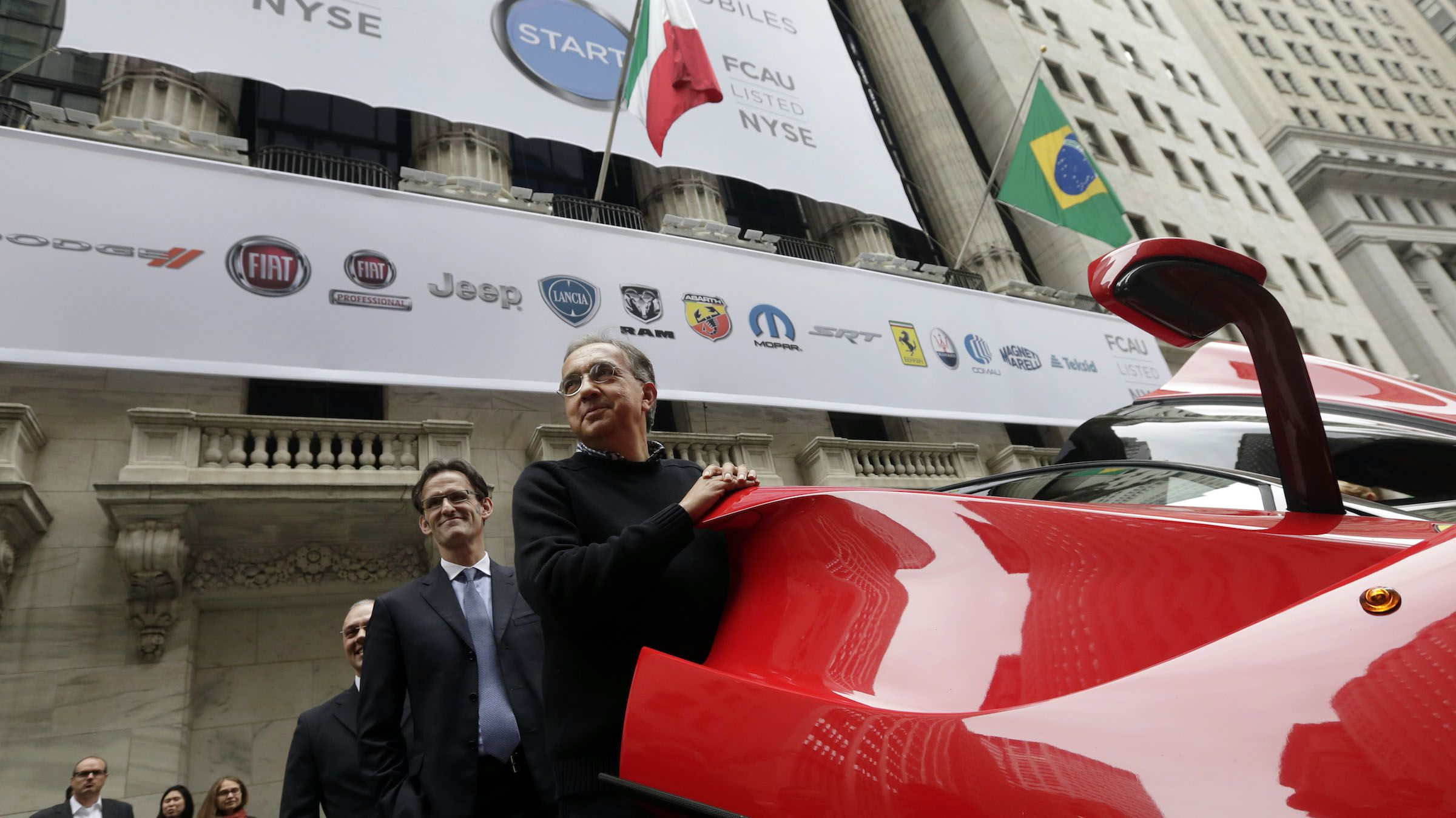 Fiat Chrysler Automobiles CEO Sergio Marchionne, right, with company CFO Richard Palmer, closes the door of a Ferrari LaFerrari, outside the New York Stock Exchange, after he rang the closing bell, Monday, Oct. 13, 2014. Shares of Fiat Chrysler Automobiles bounced between negative and positive Monday after making their debut on the New York Stock Exchange.