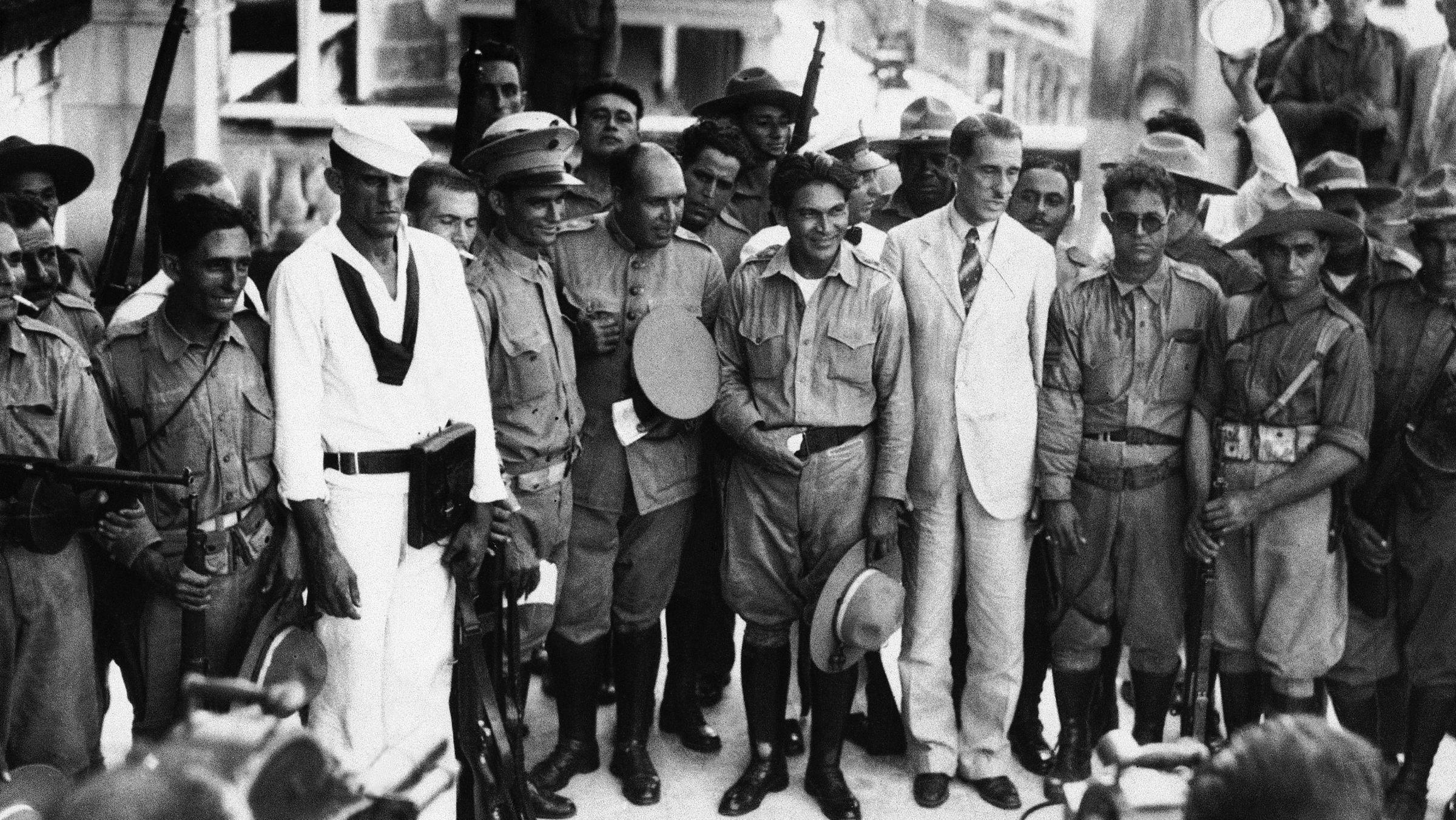 """Sergeant Fulgencio Batista, center, hand on belt, who overnight has become the center of activity in the latest Cuban trouble, is shown Sept. 7, 1933. From his place as top sergeant in the Cuban Army he took the title of """"Revolutionary Chief of Armed Forces"""" in the uprising which caused the downfall of the de Cespedes government."""
