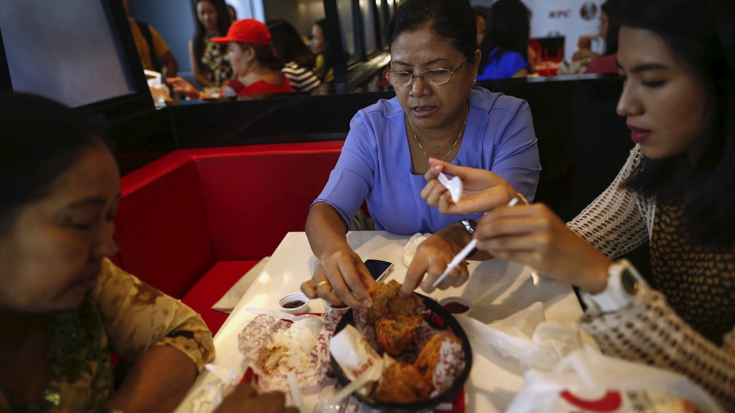Customers eat fried chicken at a KFC branch during its opening day in Yangon