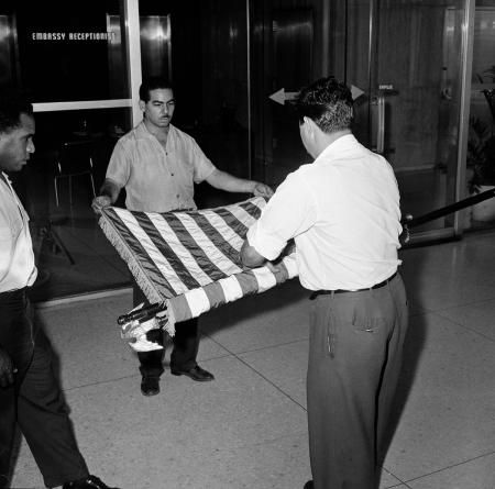 FILE - This Jan. 7, 1961 file photo shows unidentified U.S. embassy employees rolling up a U.S. flag as the embassy transfers American affairs to the Swiss government, in Havana, Cuba. The U.S. Interests Section is poised to be transformed into a full embassy, which would include such symbolic measures such as raising the American flag on the Malecon, after the U.S. and Cuba announced on Dec. 17, 2014 they are re-establishing full diplomatic relations.