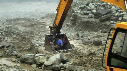 An excavator moves villagers away from a flooded area during heavy rainfall in Yingxiu, Wenchuan county, Sichuan province, July 10, 2013