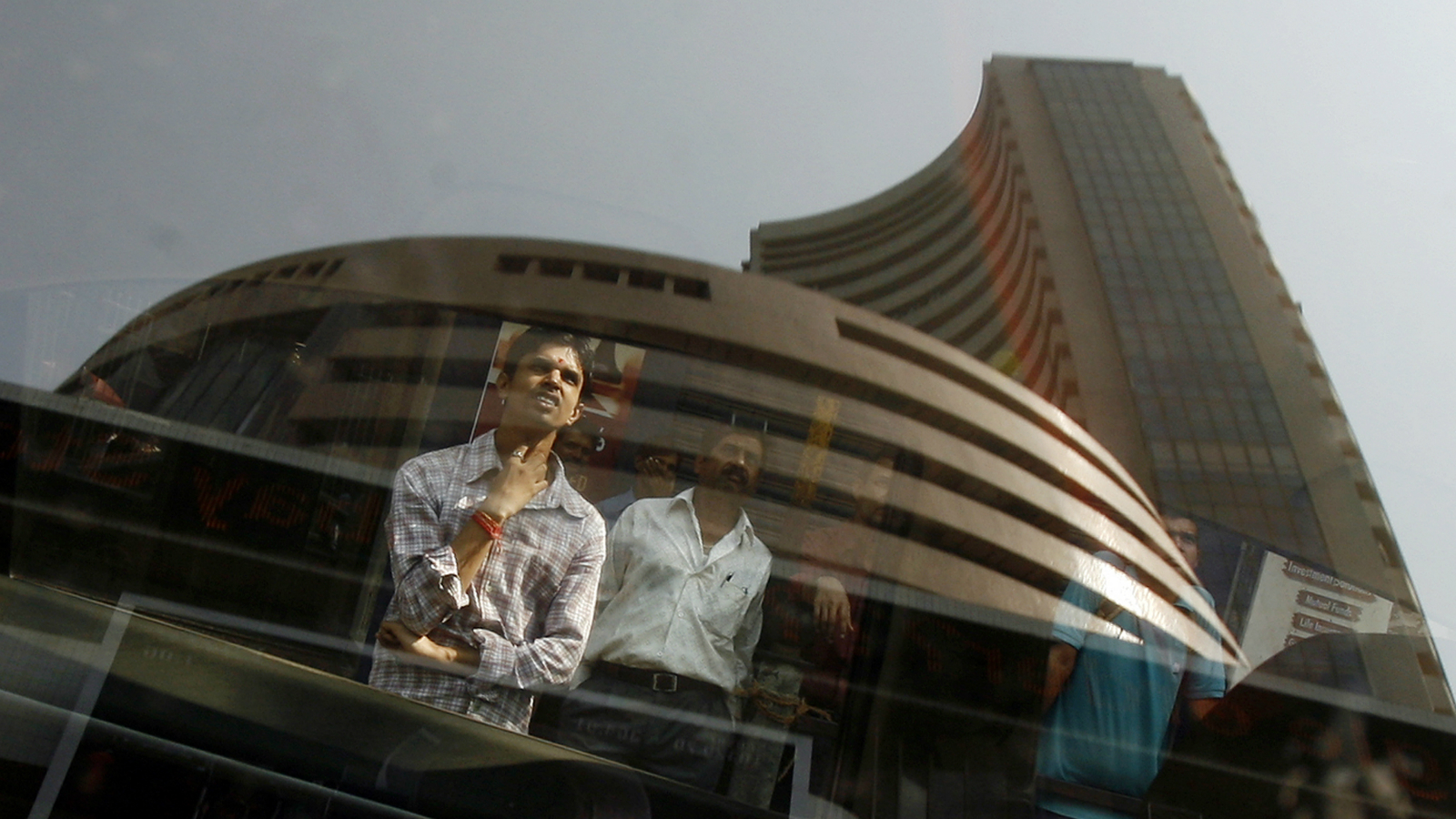 The Bombay Stock Exchange (BSE) building is reflected on a glass window as people look at a large screen displaying India's benchmark share index on the facade of the building in Mumbai November 10, 2008. REUTERS/Arko Datta (INDIA)