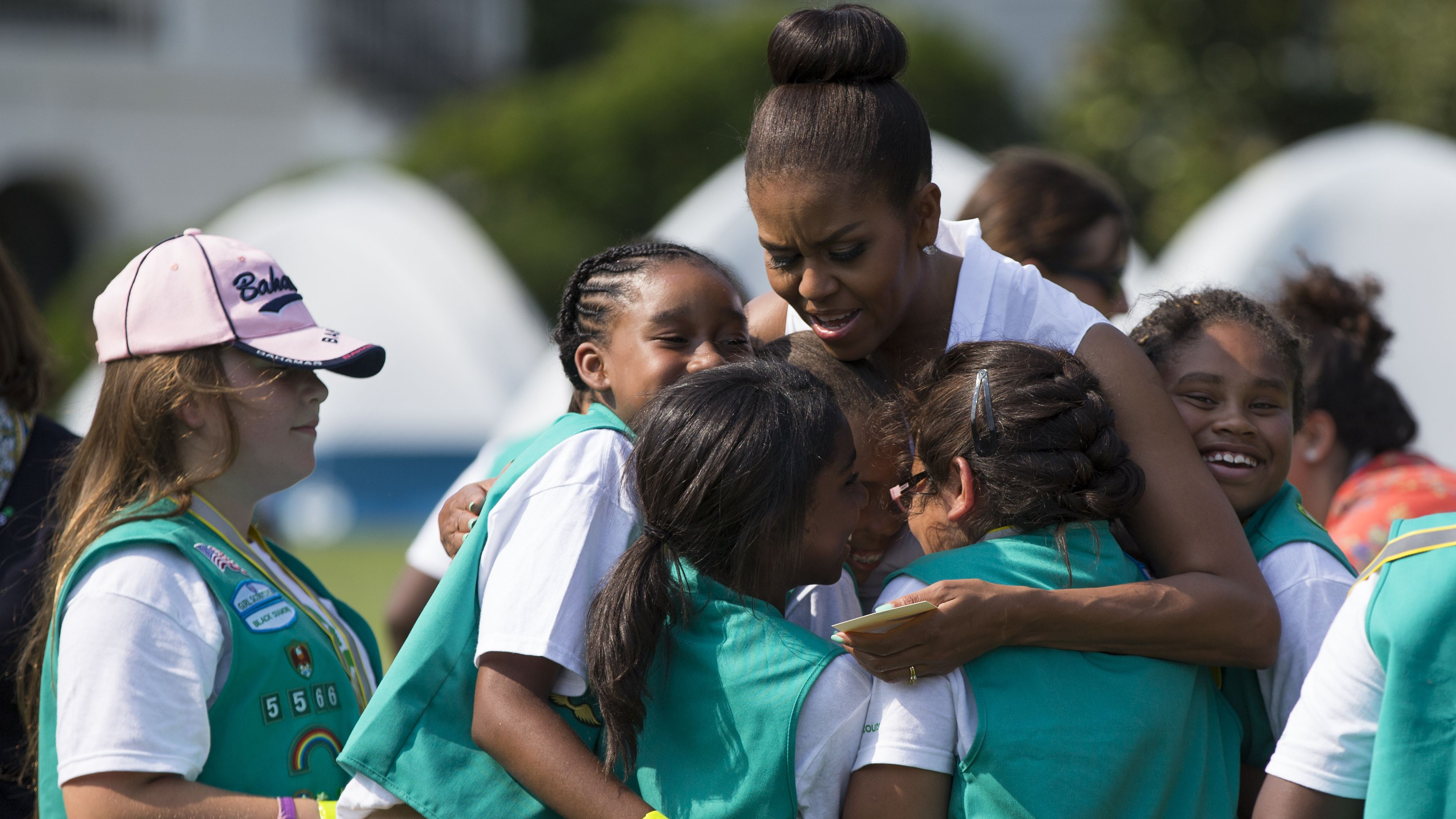First lady Michelle Obama hugs a group of Girl Scouts during a Lets Move! event on the South Lawn of the White House, on Tuesday, June 30, 2015, in Washington. Fifty fourth-grade Girl Scouts from councils in Maryland, West Virginia, Virginia, the District of Columbia and Oklahoma have been invited to spend the night sleeping in tents pitched on the South Lawn. (AP Photo/Evan Vucci)