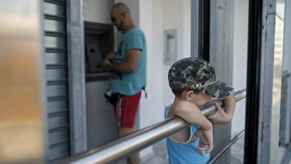 A young boy waits as his father withdraws money at an Alpha Banck branch ATM in central Athens.