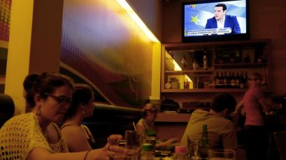 People sit at a restaurant and watch a live TV interview with the Greek Prime Minister, Alexis Tsipras.