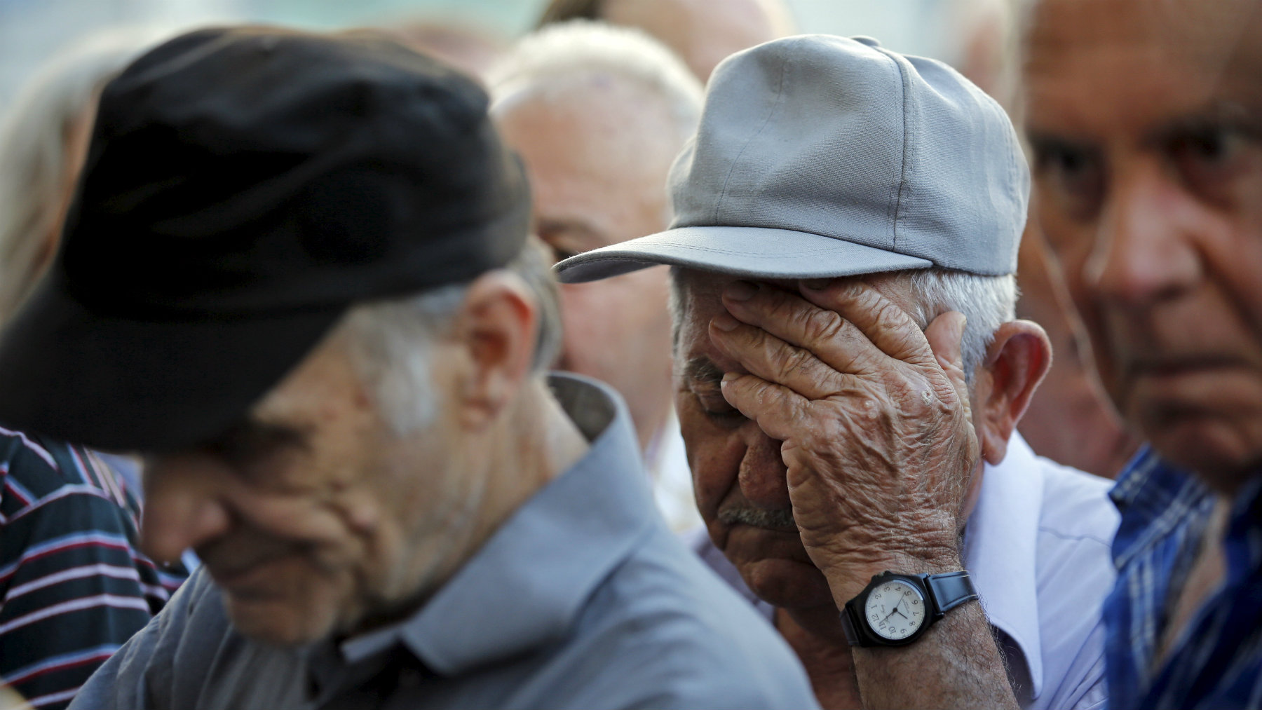 Pensioners wait in front of the main entrance of a National Bank branch to receive part of their pensions in central Athens.