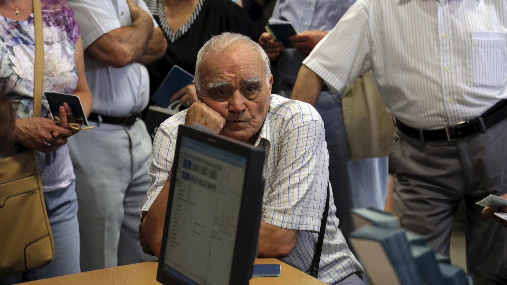 "A pensioner waits to receive part of his pension inside a National Bank branch in Iraklio on the island of Crete, Greece, July 2, 2015. A ""No"" vote in Sunday's referendum on cash-for-reforms proposals could lead to Greece leaving the euro zone, while the bloc would immediately resume work on a deal if the outcome was ""Yes,"" France's finance minister said on Thursday. REUTERS/Stefanos Rapanis"
