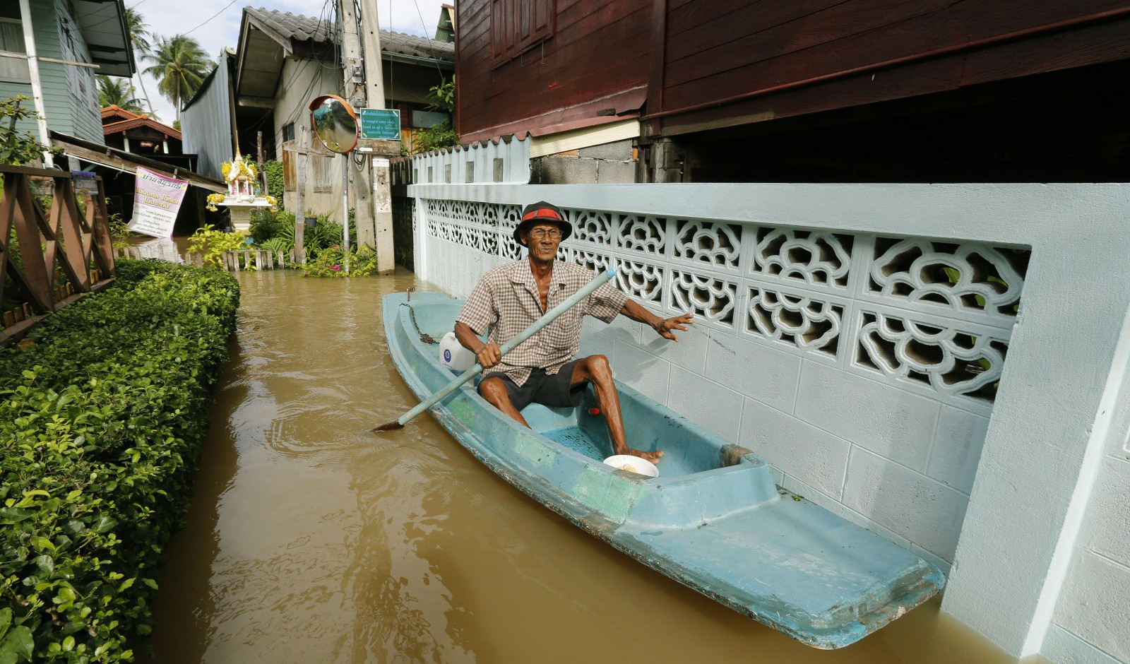 epa03901624 A Thai villager uses a boat in a flooded street on the Ko Kret island, Nonthaburi province, on the outskirts of Bangkok, Thailand, 08 October 2013. The death toll in nearly three weeks of heavy monsoon flooding in Thailand rose to at least 34 on 08 October 2013. Some 2.9 million residents reported to be affected in 33 of the 77 provinces have had their lives disrupted by the downpours and flash floods, with 4,947 roads and 201 bridges damaged, the Disaster Prevention and Relief Department said. Thailand's government has said that Bangkok would likely be spared from major flooding this year, adding that a repeat of the massive flooding of 2011, in which 813 people were killed nationwide and economic losses topped 40 billion dollars, was unlikely.  EPA/NARONG SANGNAK