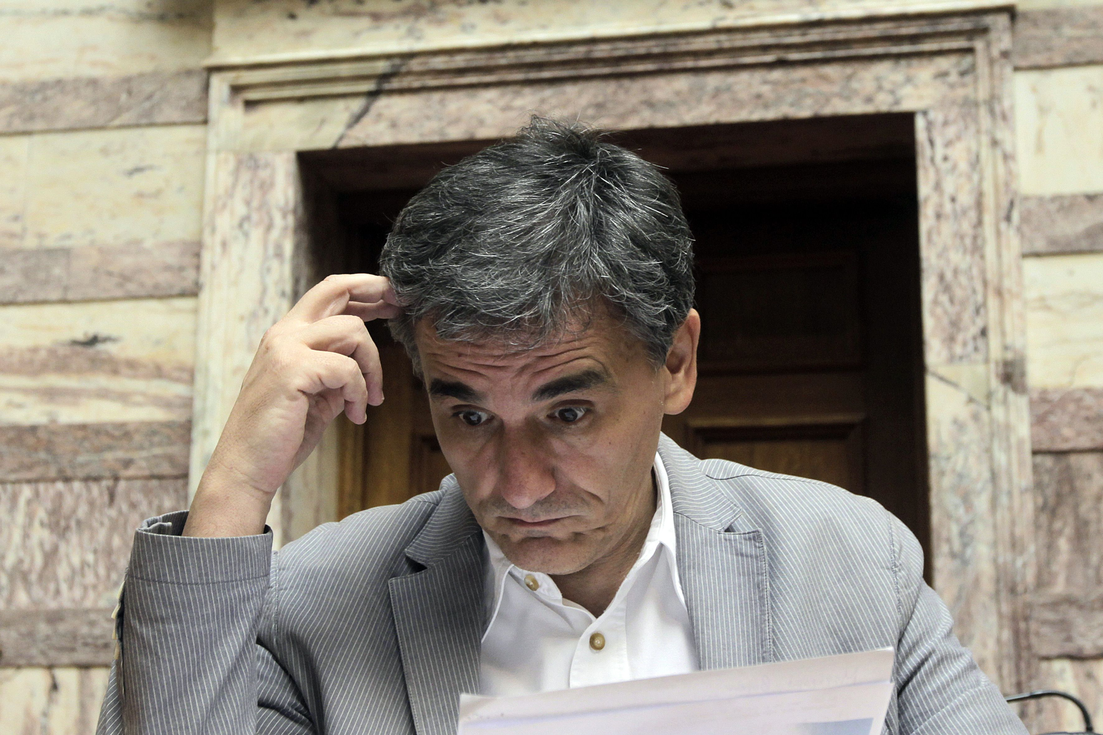 epa04840606 Greek Finance Minister Euclid Tsakalotos reads his notes in the plenumof the Greek Parliament, in Athens, Greece, 10 July 2015. The parliamentary group of governing SYRIZA party met on the proposal scheme that the government sent to its creditors. Greece's proposals were submitted to Brussels late 09 July, as part of a plan to support their request for a three-year loan. According to Greek financial website Capital.gr, the loan request is for 53.5 billion euros (59 billion dollars) from the eurozone bailout fund, the European Stability Mechanism (ESM).  EPA/ORESTIS PANAGIOTOU