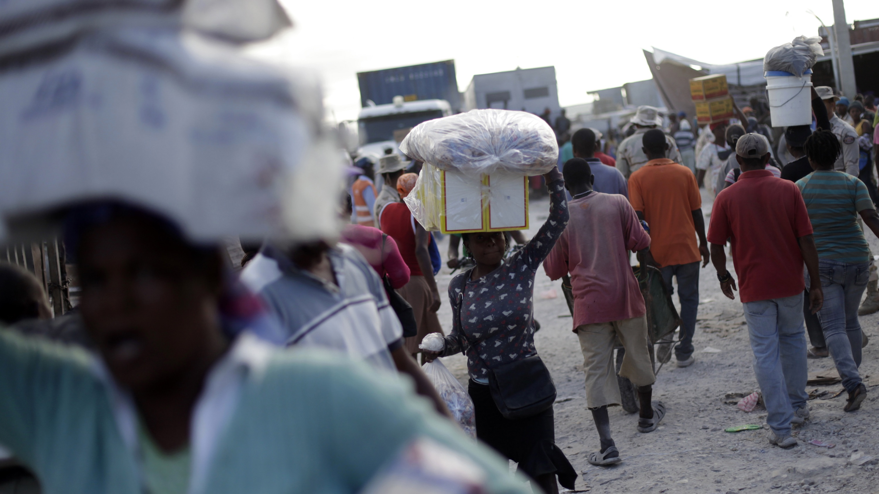 Haitian women carry goods on their heads bought in the Dominican Republic, at the border town of Malpasse, Haiti.