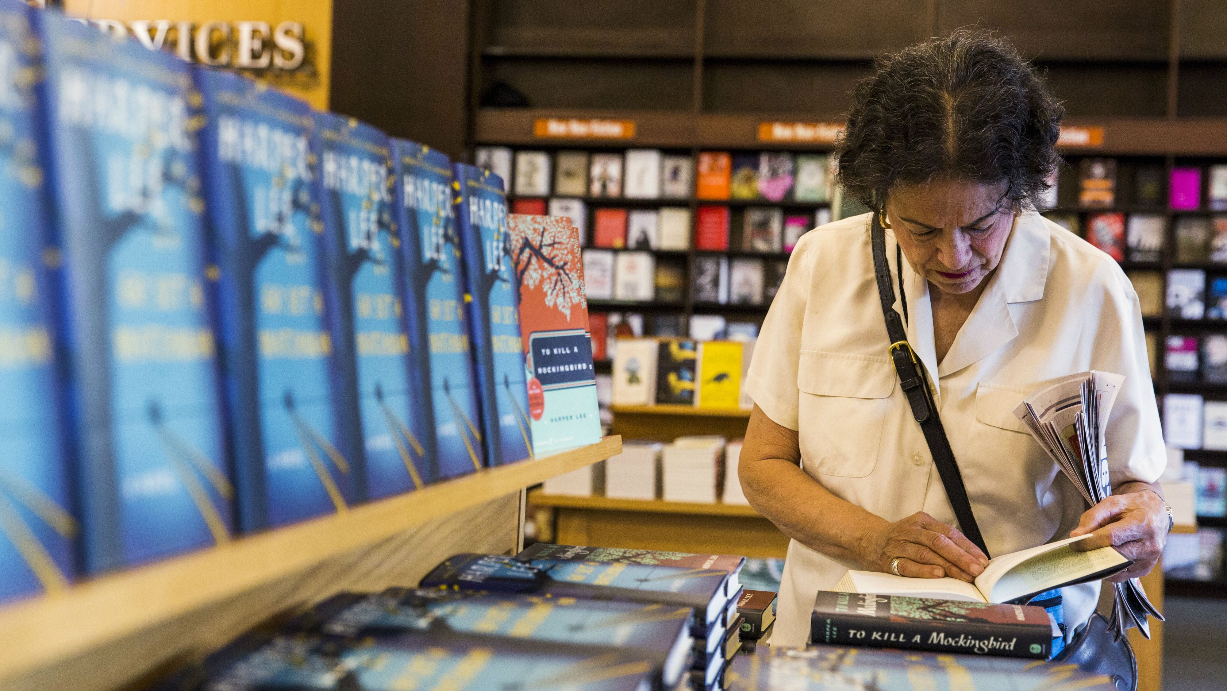 """A woman looks through """"To Kill a Mockingbird"""" before purchasing a copy of Harper Lee's book """"Go Set a Watchman"""" inside of a Barnes & Noble store in New York, July 14, 2015."""