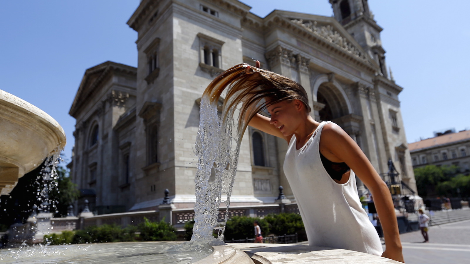 A woman dips her head into a fountain in Budapest