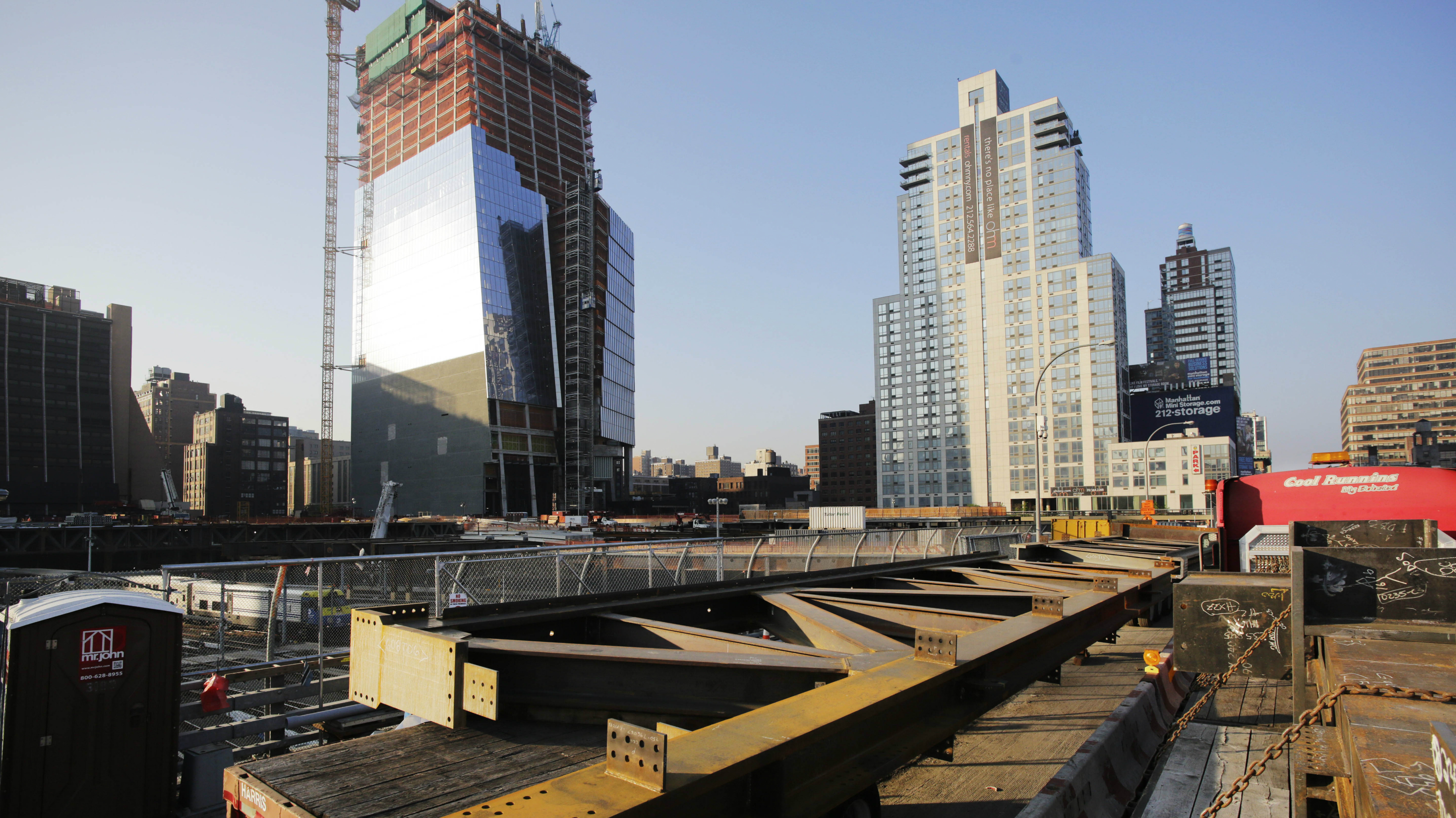 Massive steel structural pieces arrive on flatbed trucks for delivery to the Hudson Yards construction site, Friday, May 8, 2015 in New York. The steel pieces are the first shipment of a 100,000-ton steel order that will be used to complete construction of the 14-acre Eastern Rail Yard platform, a skyscraper that will house Time Warner headquarters, and a retail space with a Neiman Marcus store. The platform is being built over 30 active Long Island Rail Road (LIRR) train tracks, three subsurface rail tunnels utilized by AMTRAK and New Jersey Transit. Hudson Yards is expected to consist of 16 skyscrapers, containing new office, residential, and retail space. The tower under construction, left, is 10 Hudson Yards, the future home of Coach, L'Oreal and SAP.