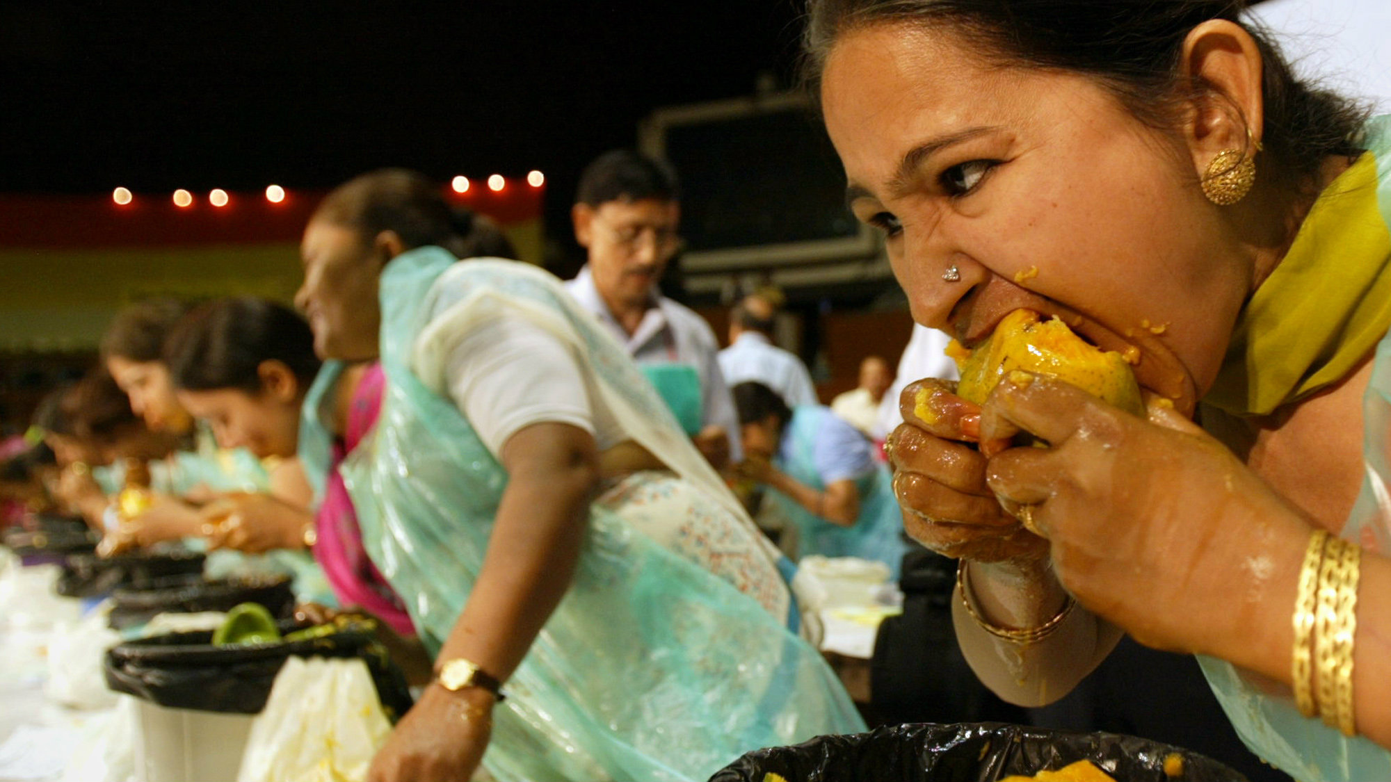 A woman eats a mango at a mango eating competition in New Delhi, India, Saturday, July 8, 2006. The contest was organized on the first day of the 18th Mango festival, where nearly 500 varieties of the fruit are on display, including the usual known varieties alphanso and safeda to the more exotic fazli, mallika and amrapali.