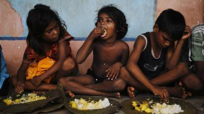 Children eat their lunch in a free meal centre at the cyclone-hit Gopalpur village, in Ganjam district in the eastern Indian state of Odisha October 14, 2013.