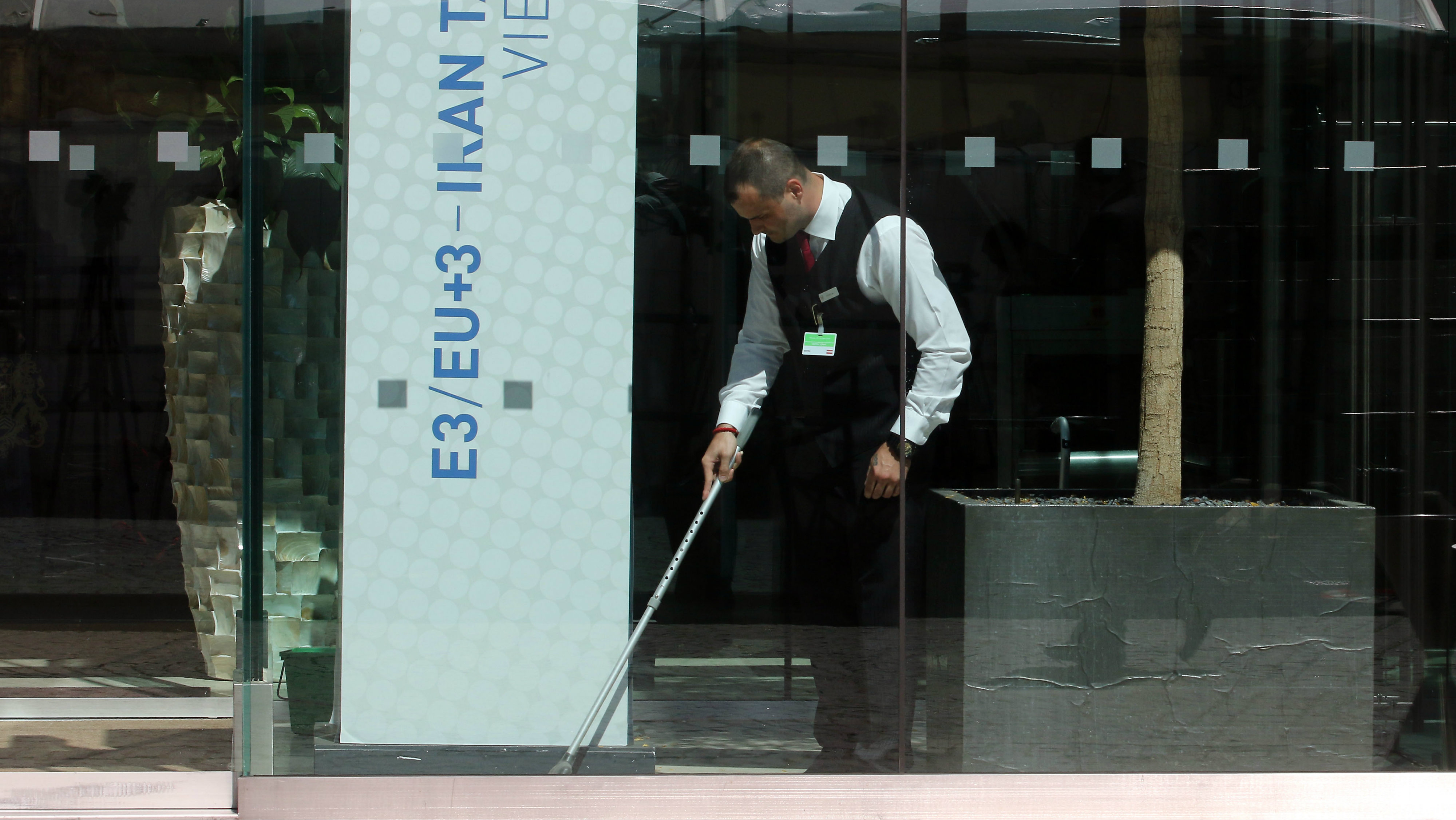 A man cleans the entrance of Palais Coburg where closed-door nuclear talks with Iran take place in Vienna, Austria, Saturday, July 11, 2015.