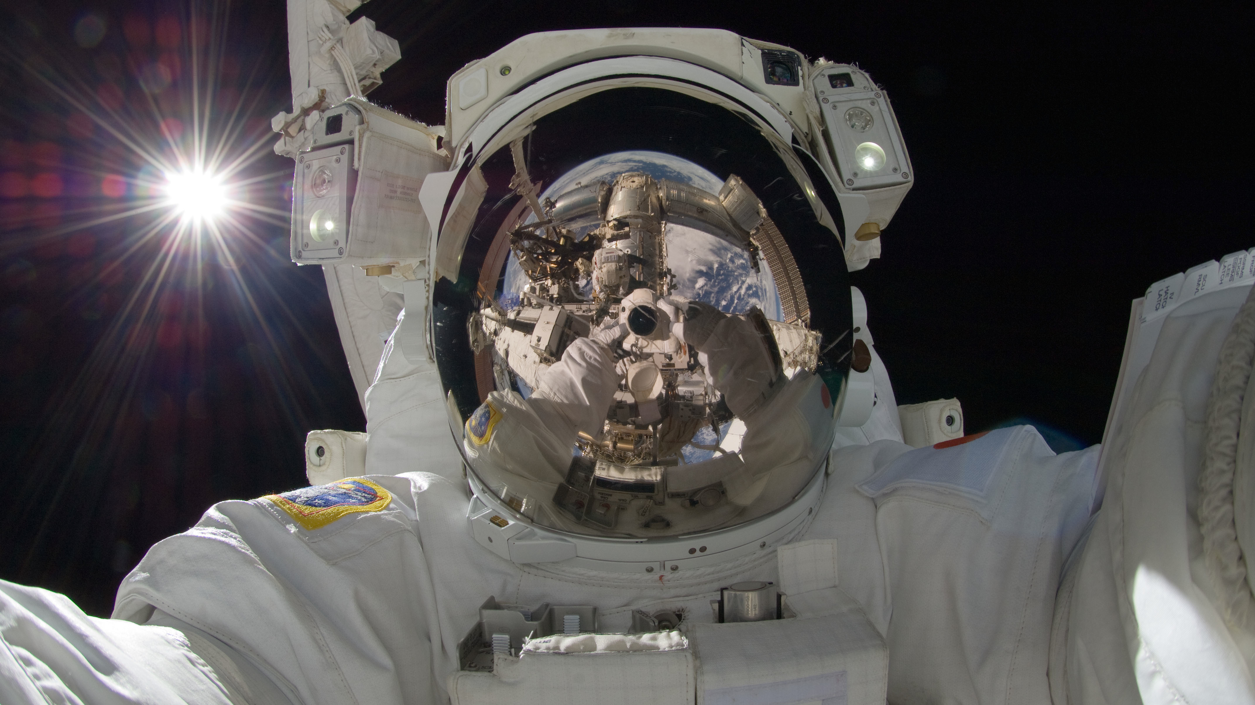 ISS032-E-025258 (5 Sept. 2012) ---Japan Aerospace Exploration Agency astronaut Aki Hoshide, Expedition 32 flight engineer, uses a digital still camera to expose a photo of his helmet visor during the mission's third session of extravehicular activity (EVA). During the six-hour, 28-minute spacewalk, Hoshide and NASA astronaut Sunita Williams (visible in the reflections of Hoshide's helmet visor), flight engineer, completed the installation of a Main Bus Switching Unit (MBSU) that was hampered last week by a possible misalignment and damaged threads where a bolt must be placed. They also installed a camera on the International Space Station's robotic arm, Canadarm2. The bright sun is visible at left.