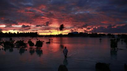A villager wades through a small lagoon, which at high-tide laps at the base of homes, near the village of Tangintebu on South Tarawa in the central Pacific island nation of Kiribati May 25, 2013.