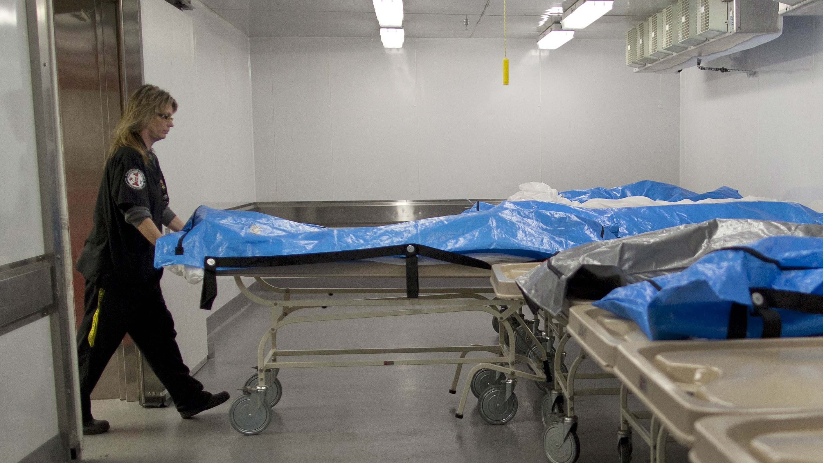 Forensic assistant Sue Miele returns a corpse to cold storage after taking x-rays of the body to help determine cause of death, Thursday, Sept. 29, 2011, at the Clark County Coroner's office in Las Vegas. The coroner's office investigates about 3,500 of the14,000 people who die each year in and around Las Vegas.The official whose name goes on thousands of death certificates each year recently inked a deal with a the Discovery Channel for a series of TV episodes featuring the work of the Sin City coroner's office.